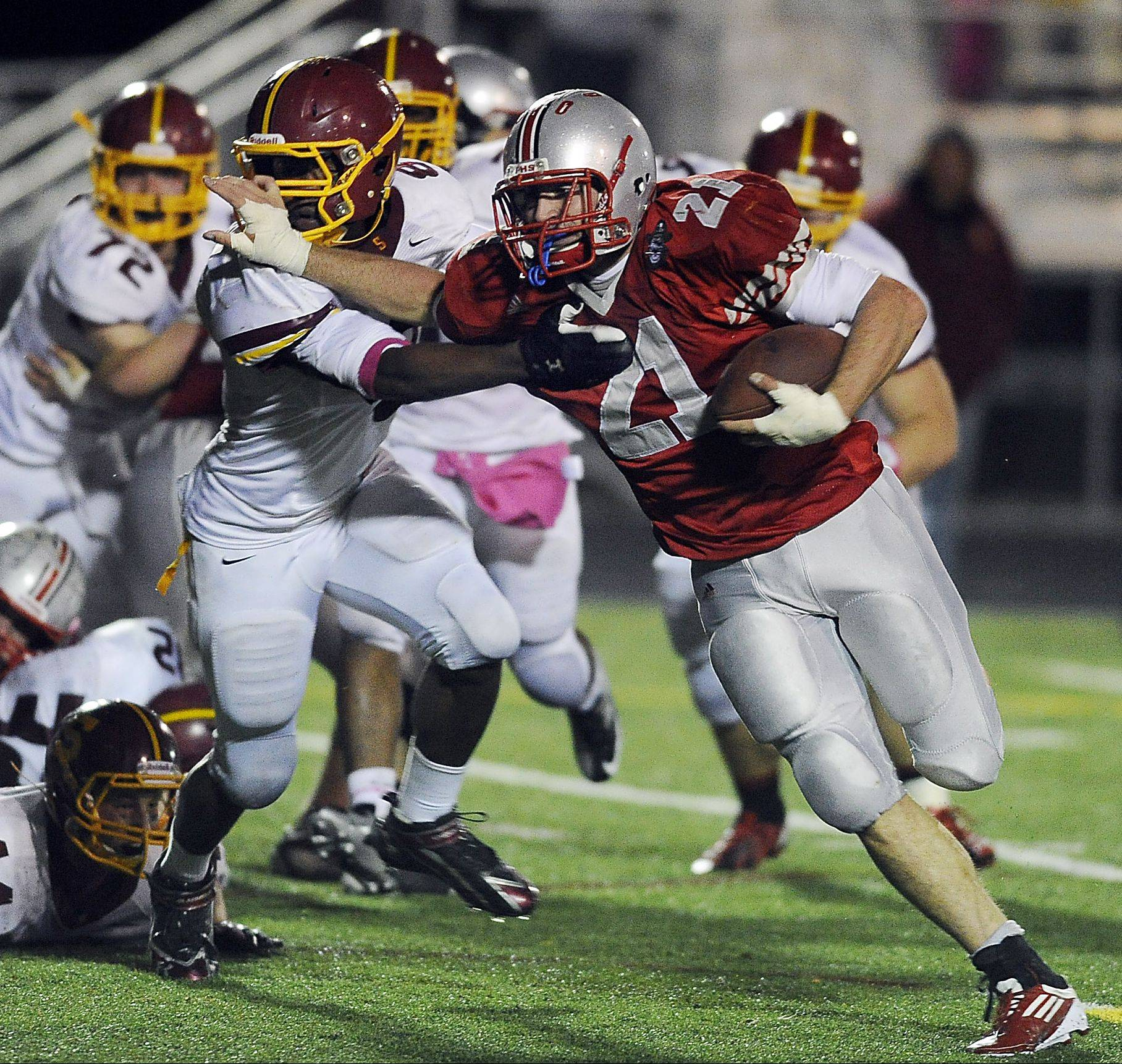 Palatine�s John Serio fights off a Schaumburg defender on a first-half touchdown run to help the Pirates top Schaumburg 51-18 and clinch an outright championship in the Mid-Suburban West.