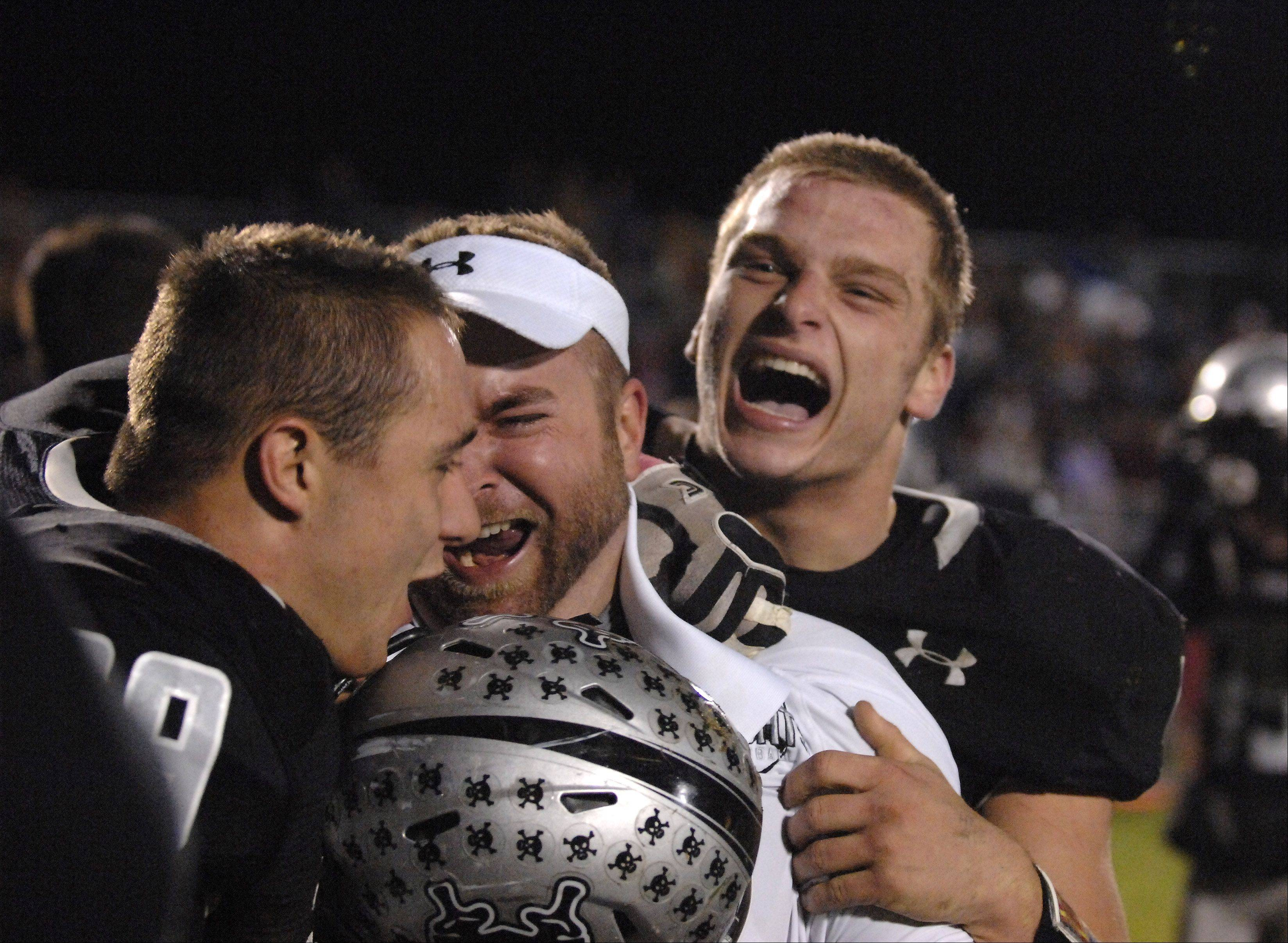 Kaneland�s Ryan Lawrence, left, and Gary Koehring, right, hug assistant coach Keith Snyder after a win over Morris Friday in Maple Park.