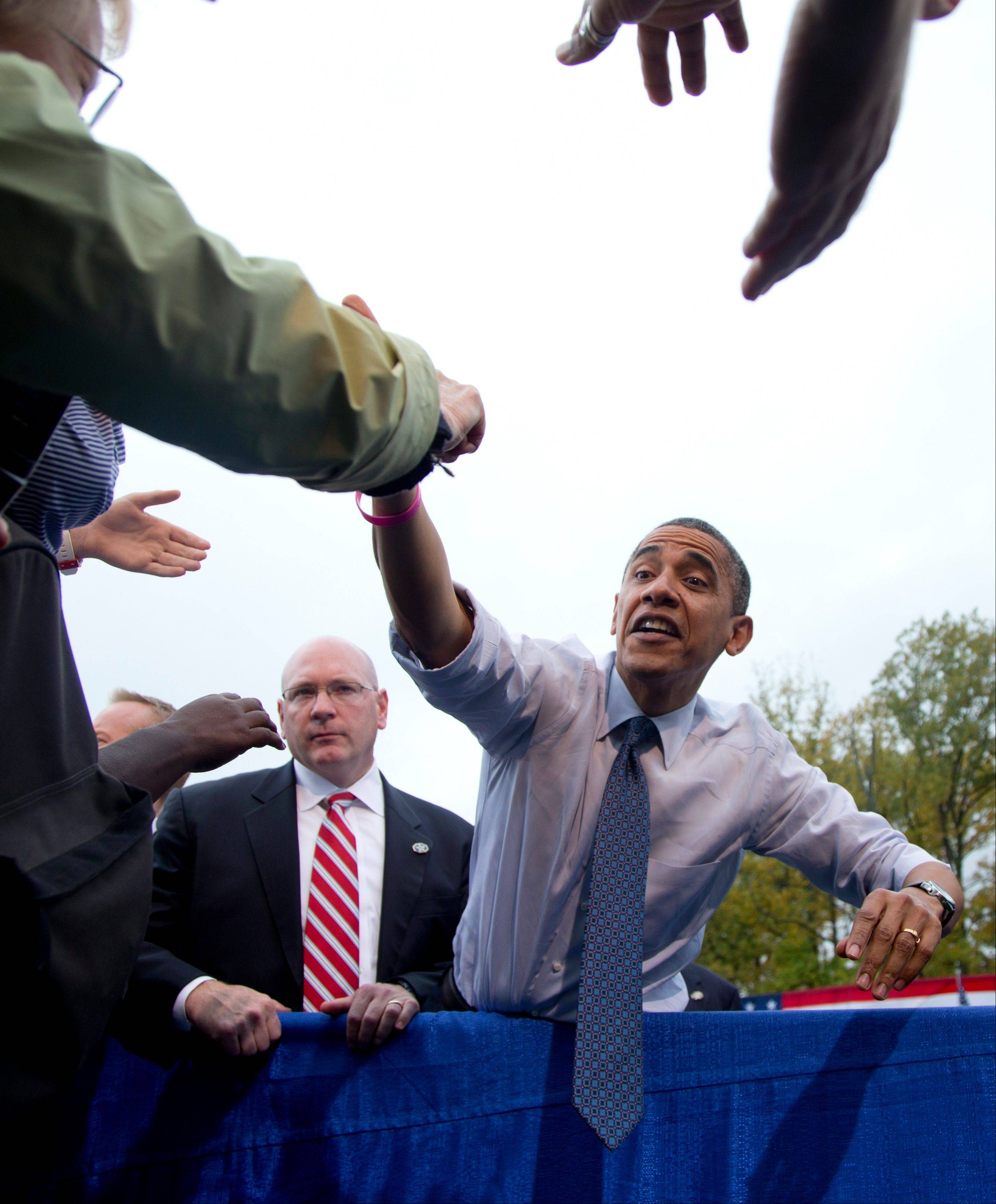 President Barack Obama stretches to shakes hands Friday with supporters after speaking about the choice facing women in the upcoming election, at George Mason University, in Fairfax, Va.