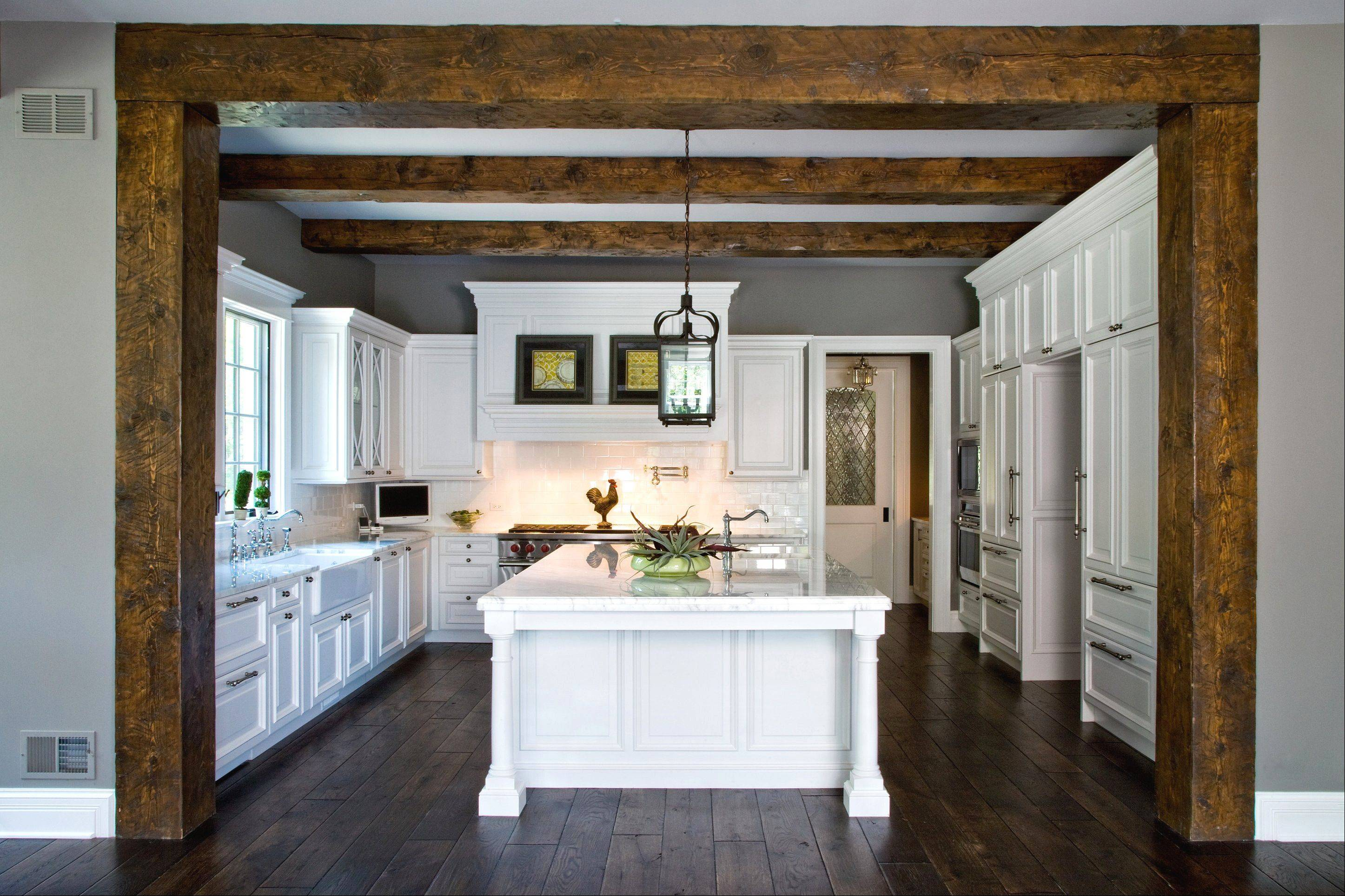 Reclaimed wood beams complement the CabinetWerks custom kitchen complete with state-of-the-art appliances.