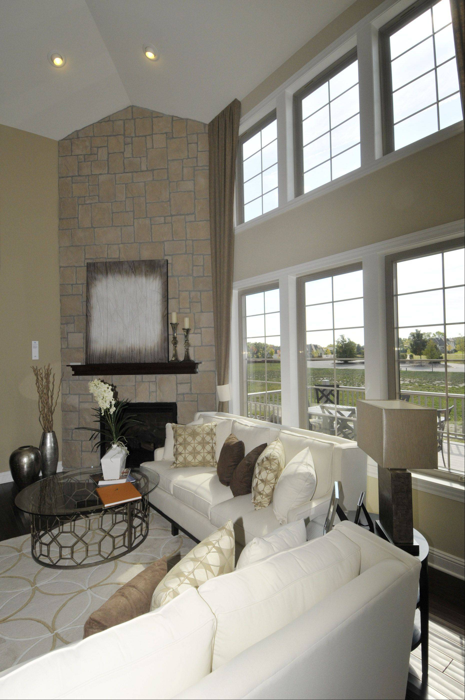 In the family room, a corner stone fireplace and a wall of windows provide the focal point.
