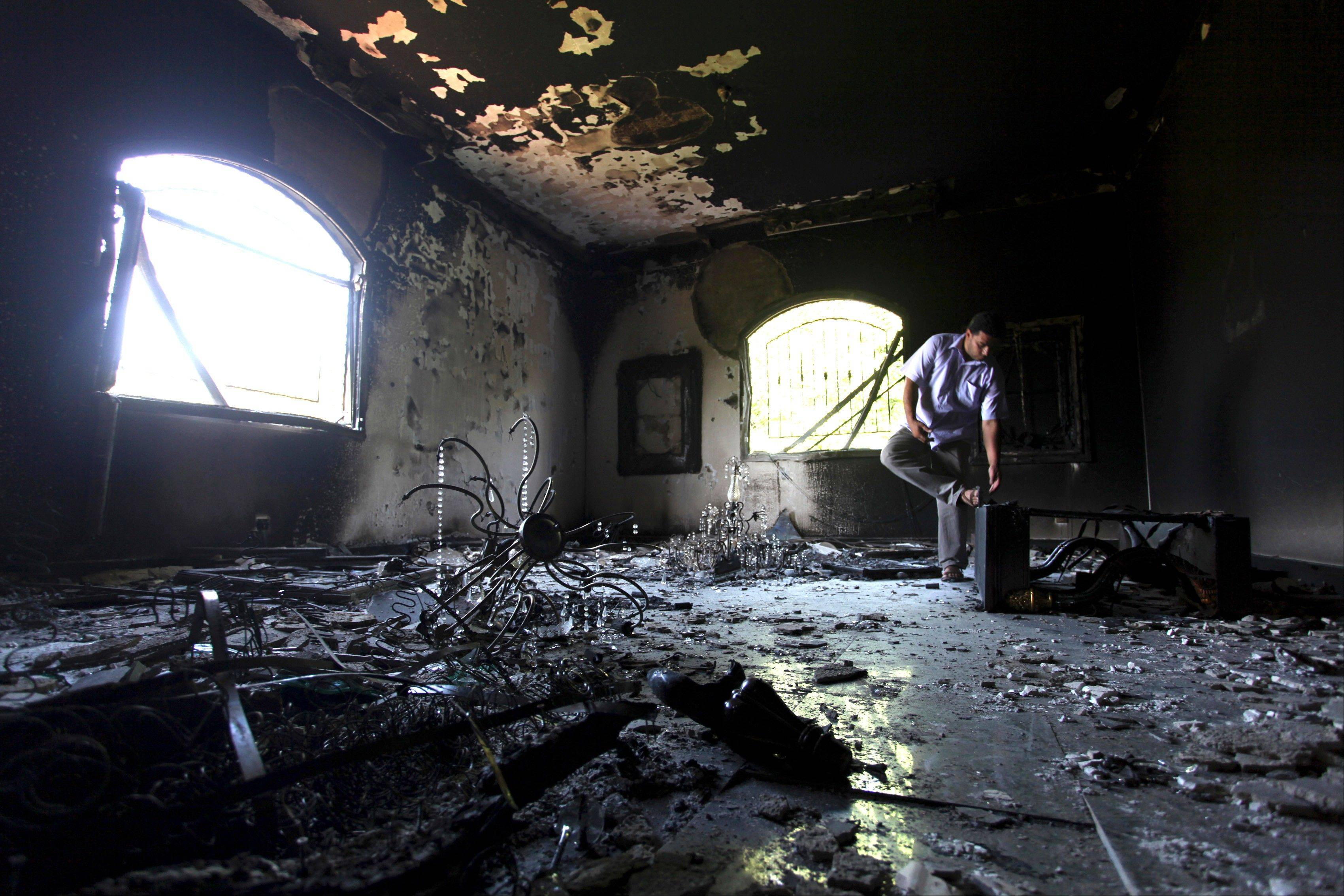 In this Sept. 13, 2012 file photo, a Libyan man investigates the inside of the U.S. Consulate, after an attack that killed four Americans, including Ambassador Chris Stevens on the night of Tuesday, Sept. 11, 2012, in Benghazi, Libya. U.S. officials tell The Associated Press that the CIA station chief in Libya reported to Washington within 24 hours that there was evidence it was carried out by militants.