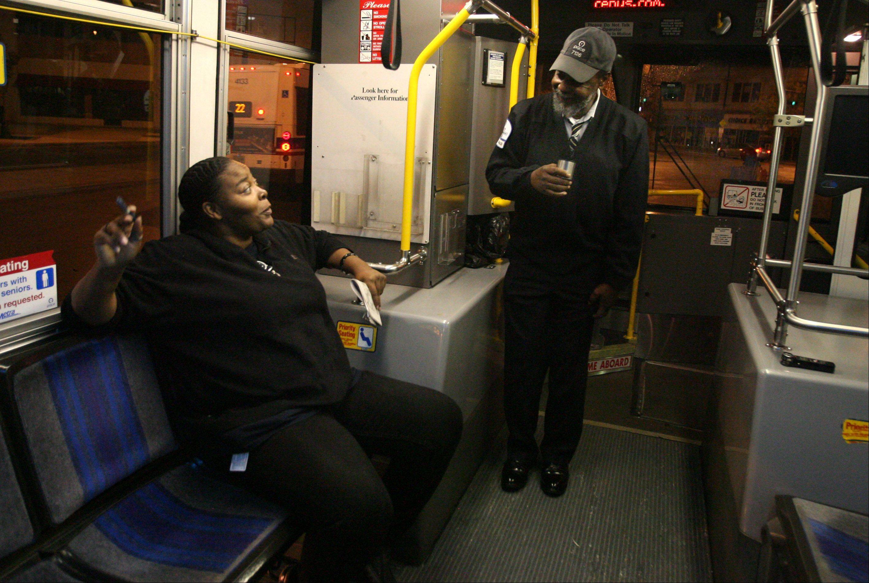 Route 290 Pace bus operator Michael Brown enjoys a cup of homemade coffee from his silver thermos while talking with passenger Hyacinth Taylor during a 10-minute break at the Howard CTA Red Line station in Evanston.