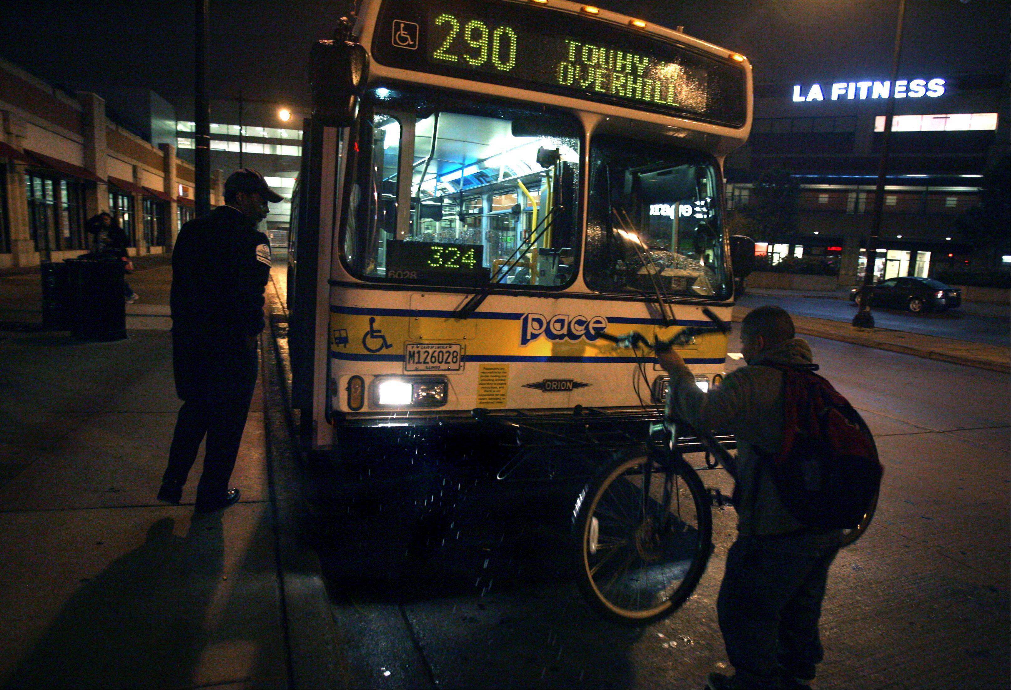 Route 290 Pace bus operator Michael Brown gets back on his bus after helping a passenger lower the bike rack at the Howard CTA Red Line station in Evanston.