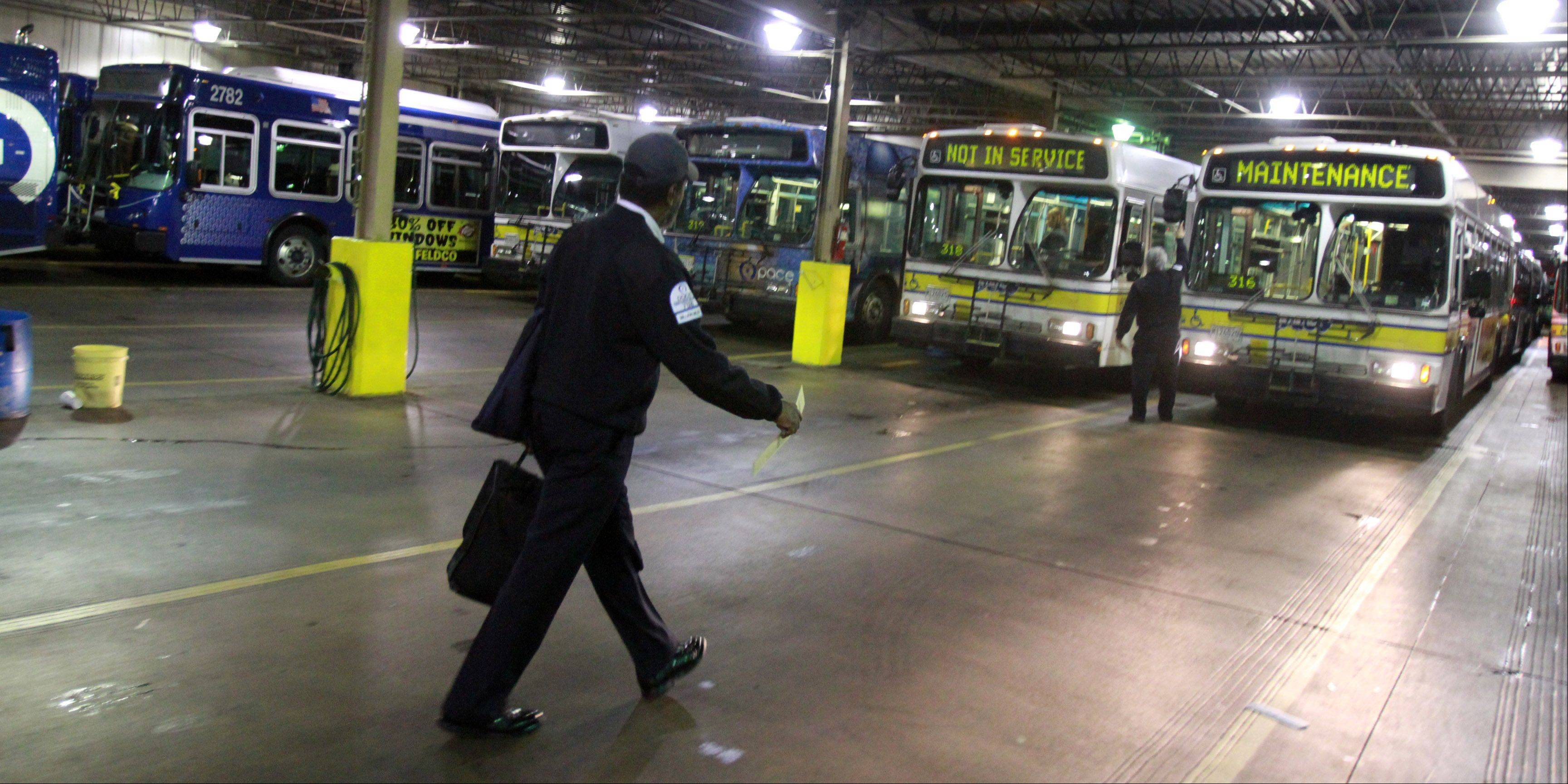 Michael Brown walks through the Pace Northwest Division garage to inspect his bus at 5:30 a.m. before starting his shift.