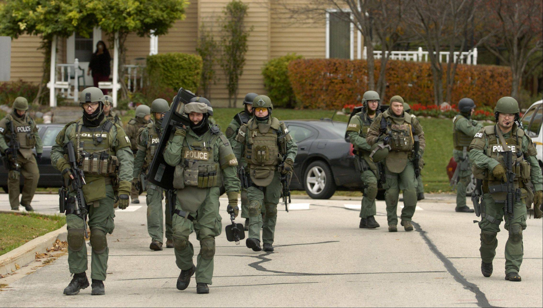 Members of the Northern Illinois Police Alarm System leave the scene of a police standoff Friday on Raven Court in Gurnee.