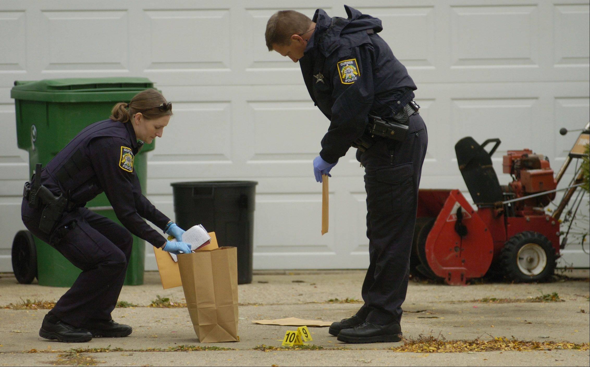 Police gather evidence in front of a home on Raven Court in Gurnee, where authorities say a Zion man fired shots at four people before keeping police at bay for several hours Friday.
