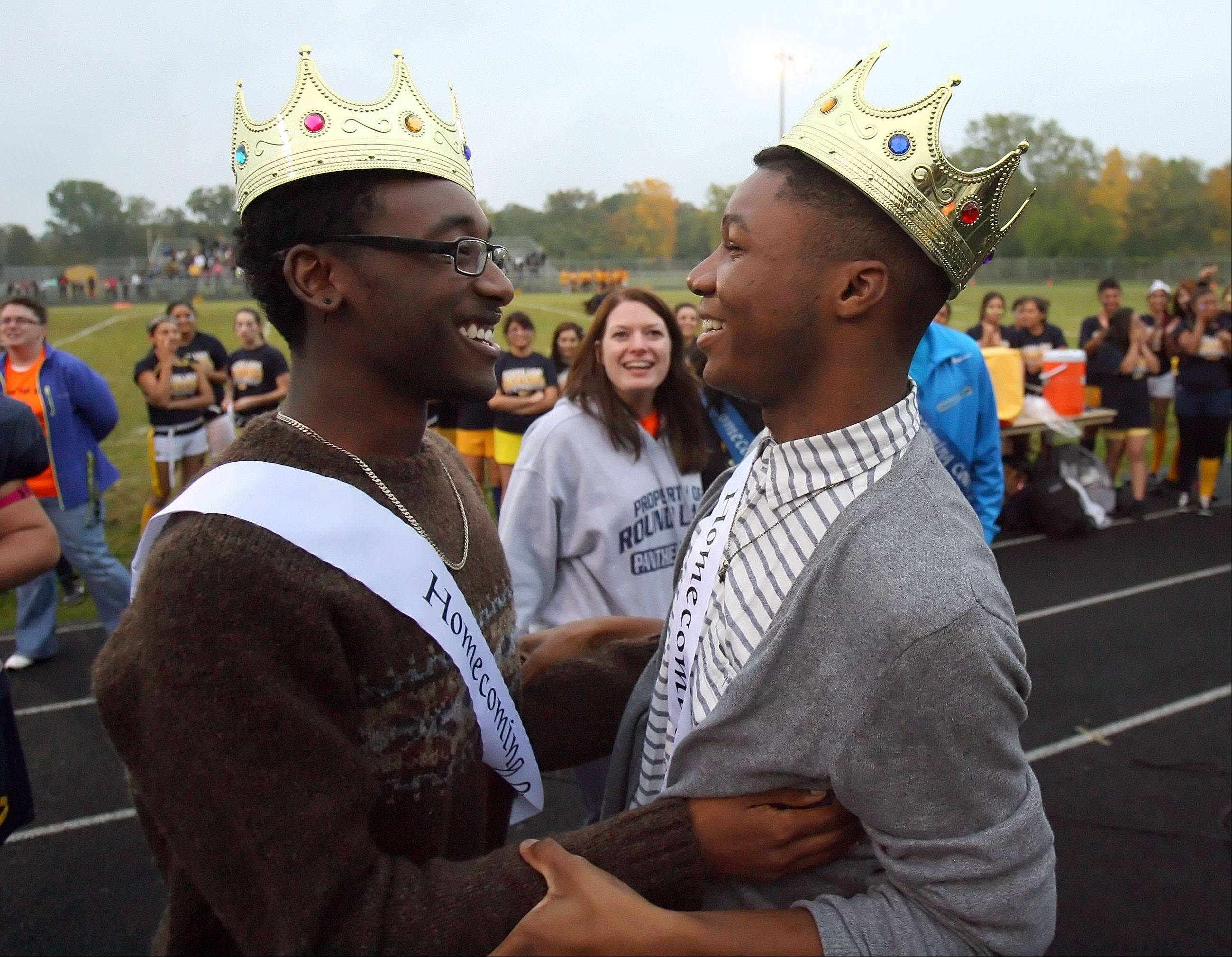 Bryant Jenkins, left, and Bougest Sutton hug after being crowned as Round Lake High School's first same-sex homecoming king and queen during halftime of the Powder-Puff Extravaganza.