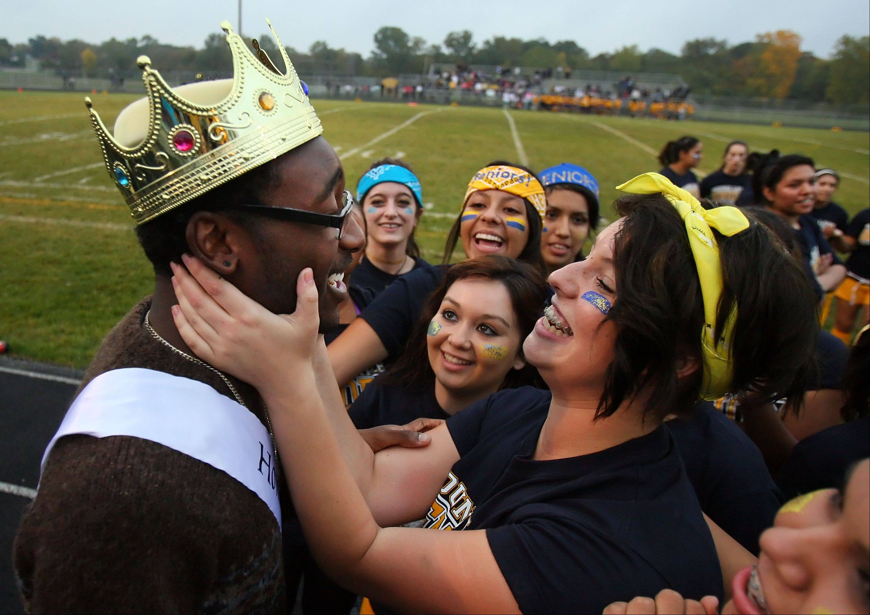 Bryant Jenkins, left, is mobbed by classmates after he and his partner Bougest Sutton, both male, were crowned homecoming royalty during halftime of the Powder-Puff Extravaganza at Round Lake High School.