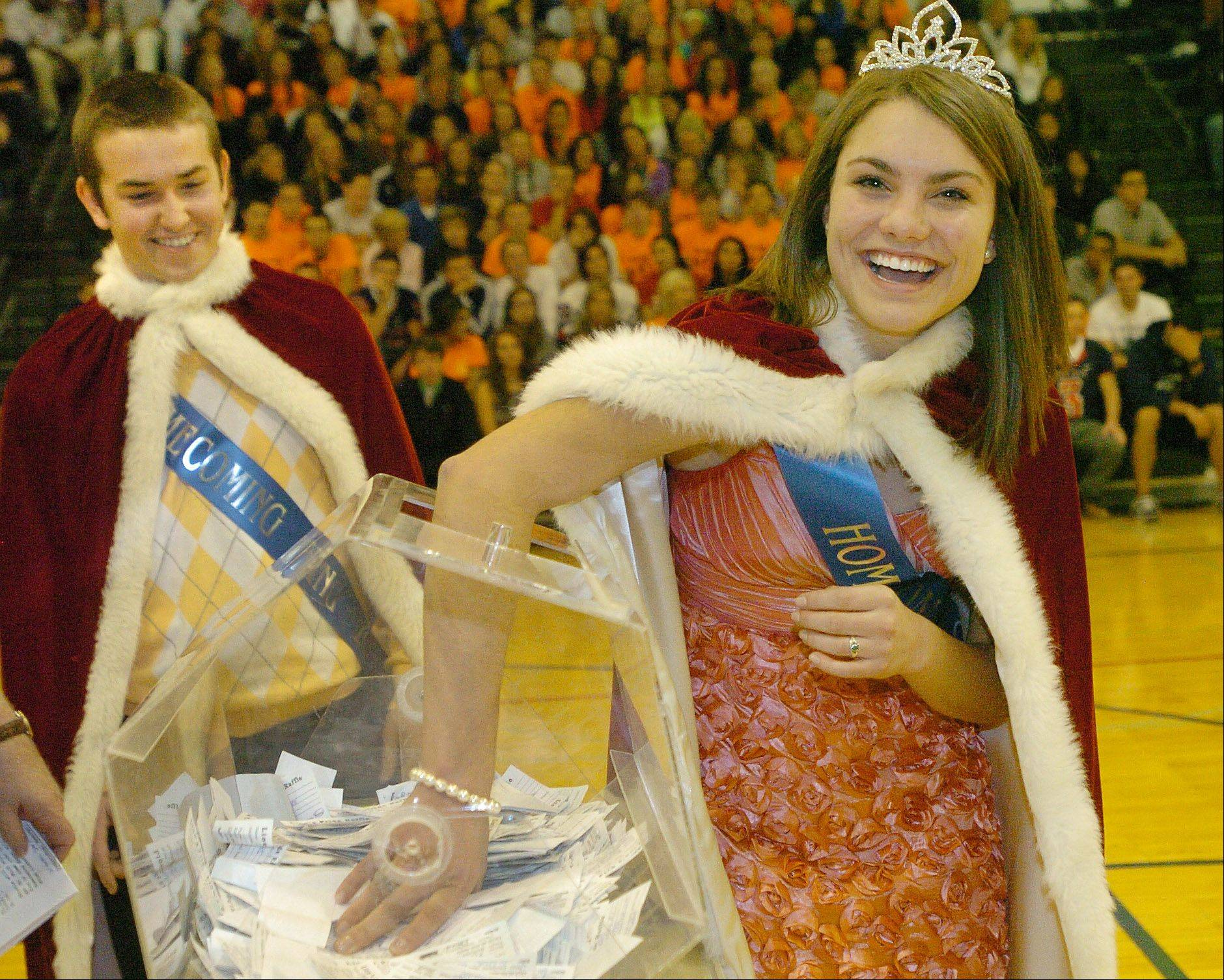 Emma Hogaboom and Tommy Sullivan draw for a winner in the Lion's Pride student fundraiser after being crowned King and Queen during St. Viator's Homecoming Pep Rally.