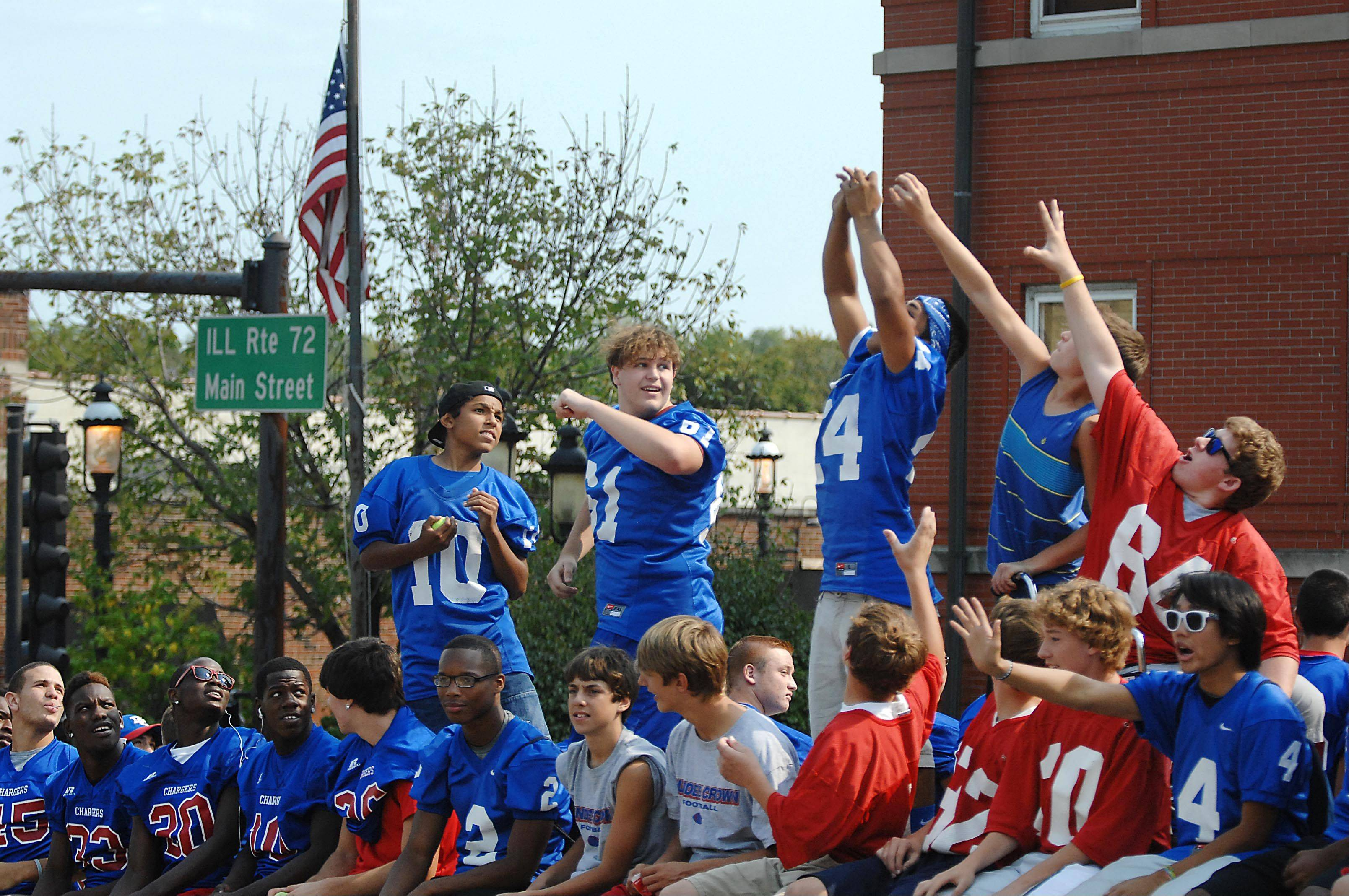 Varsity football players reach for a tennis ball thrown from the crowd at the Dundee-Crown High School Homecoming Parade on Main Street in West Dundee. The parade started in East Dundee and crossed the Fox River to Grafelman Park.