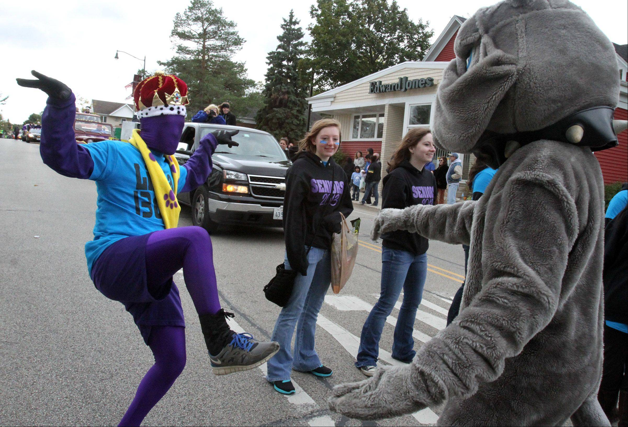 Ryan Geary, wearing a Mr. Bulldog crown, and Erik Molenda, in bulldog costume, dance around while marching in Wauconda High School's Homecoming parade.