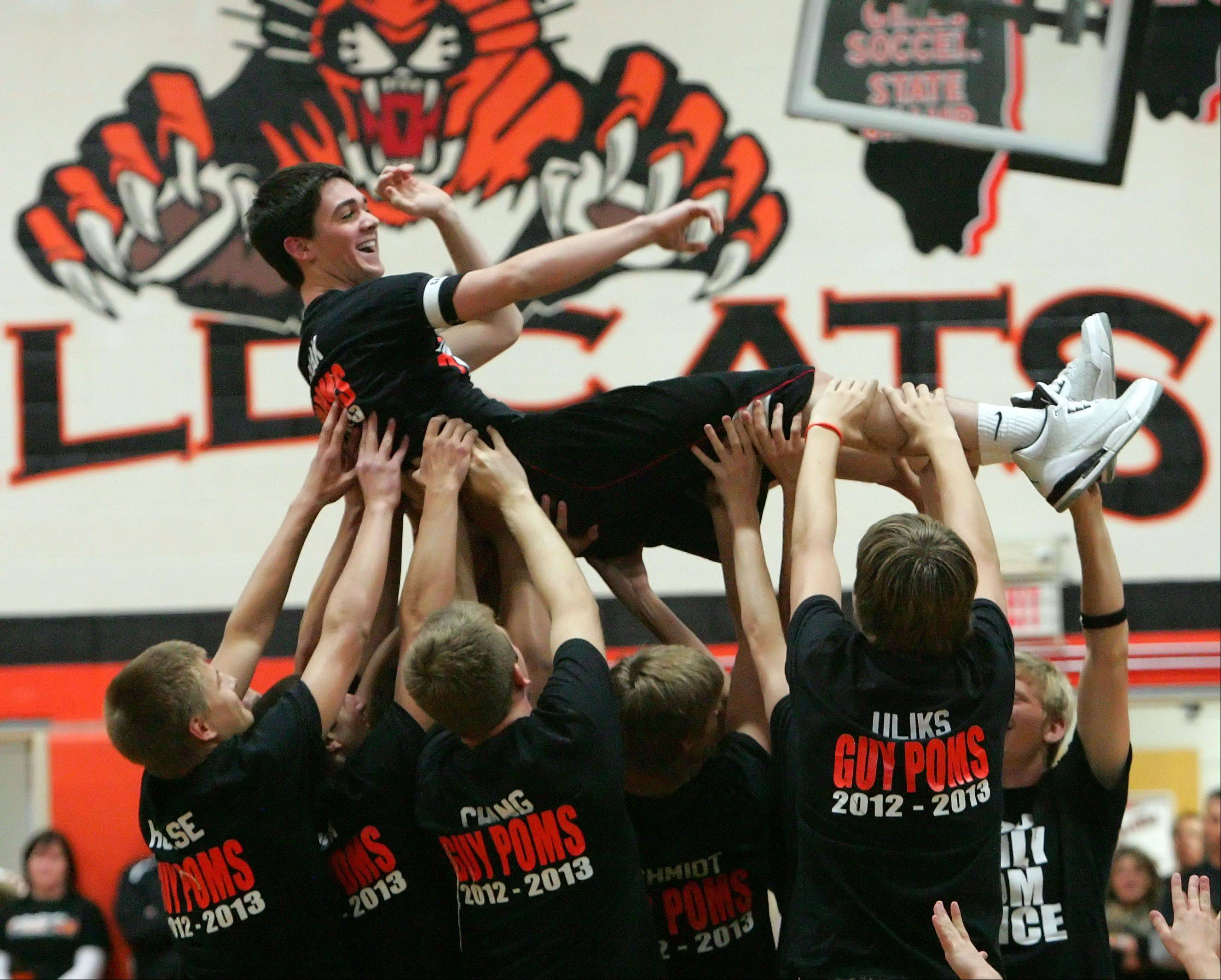 Libertyville High School senior Scott Johns is hoisted up by guy poms during their Homecoming pep rally.