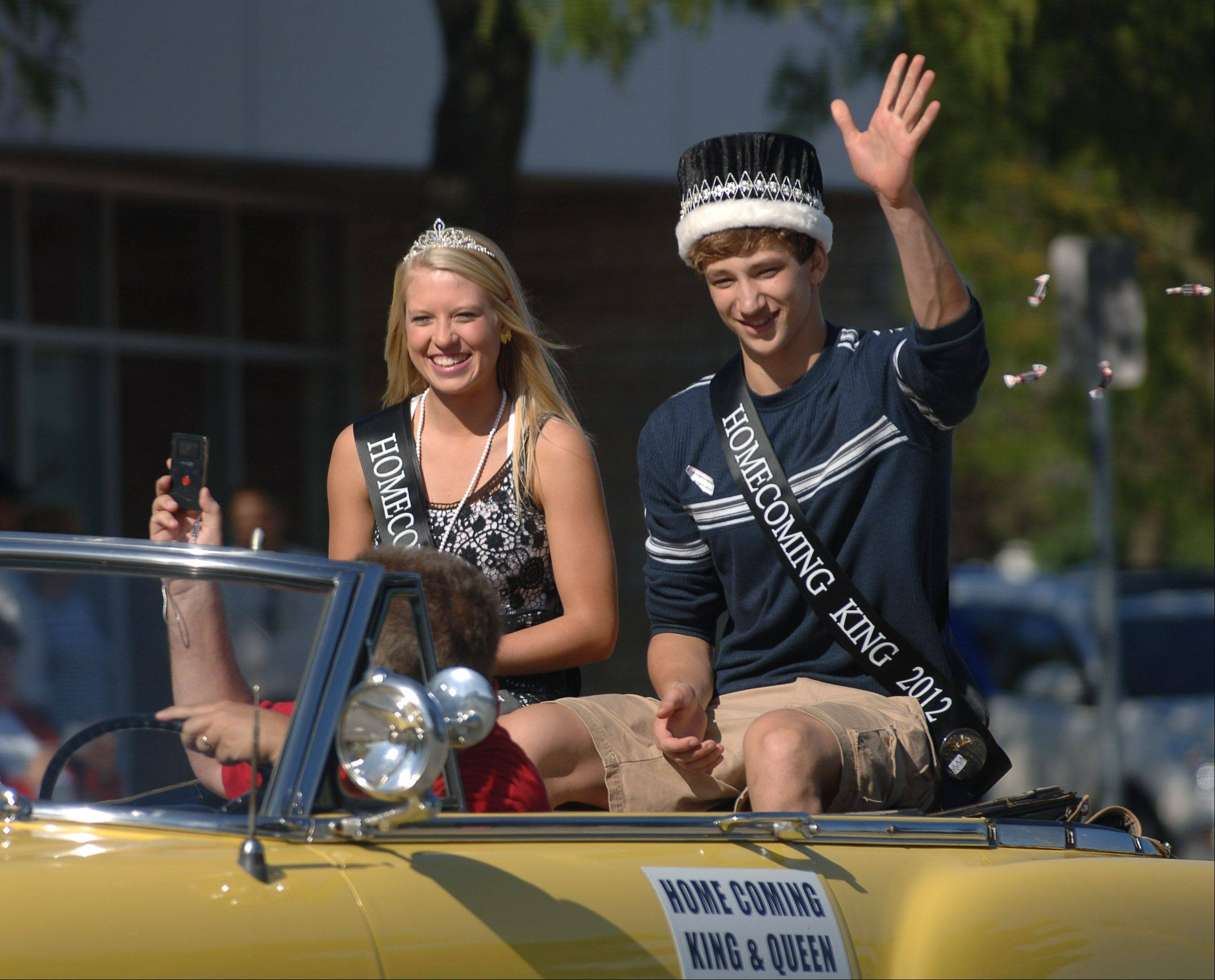 Mundelein High School's homecoming queen Chloe Peterson of Wauconda, and king Connor Black of Mundelein, toss candy to the crowd during the Homecoming parade through downtown Mundelein.