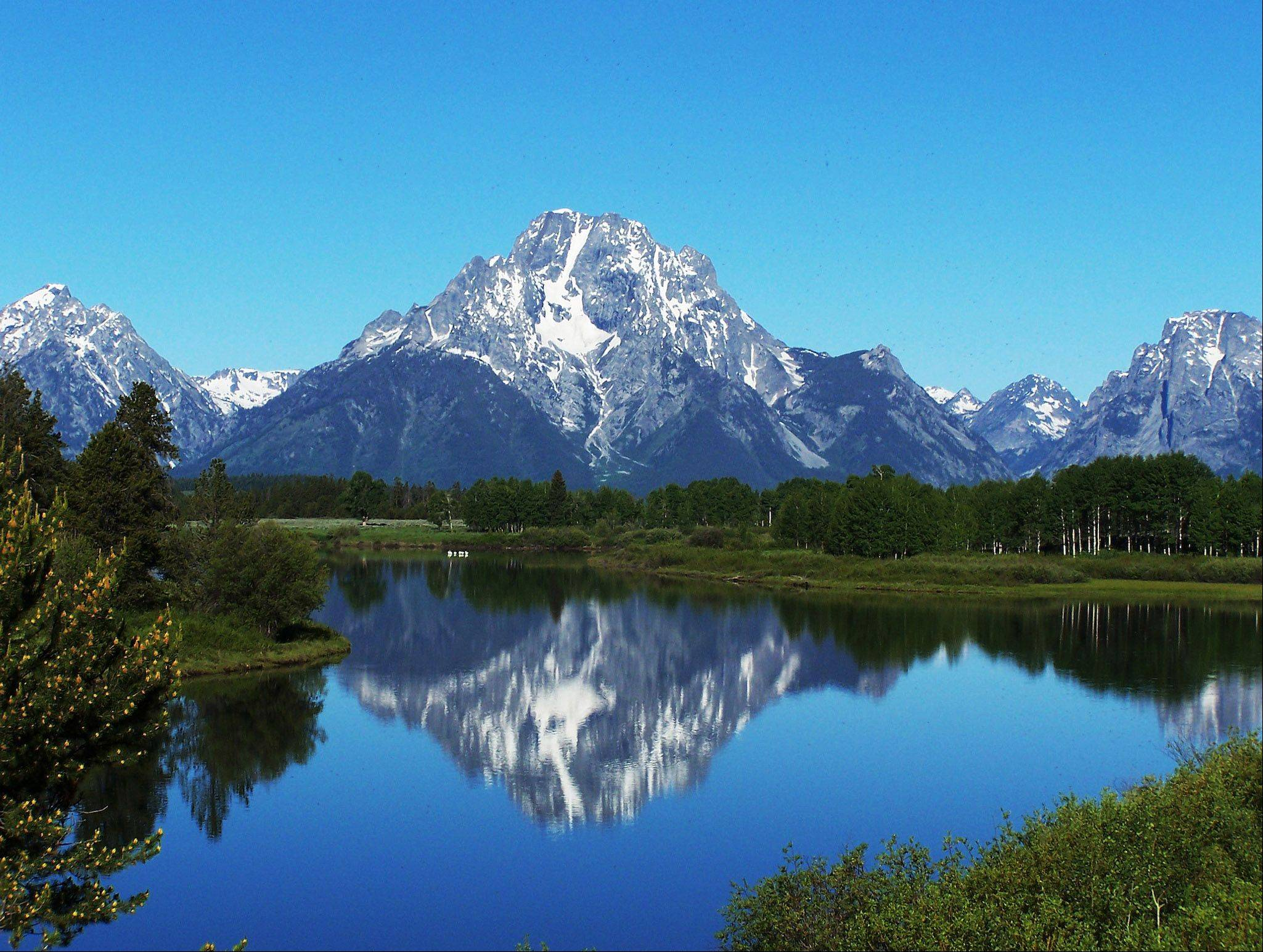 The peaks of the Grand Tetons can be seen from a lake at Ox Bow, Wyoming in 2006.