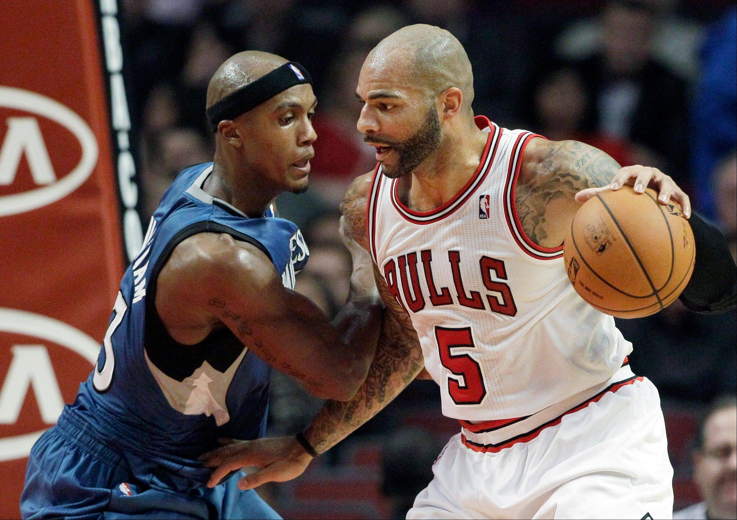 Carlos Boozer controls the ball as Minnesota's Dante Cunningham guards during the first half at the United Center on Friday.