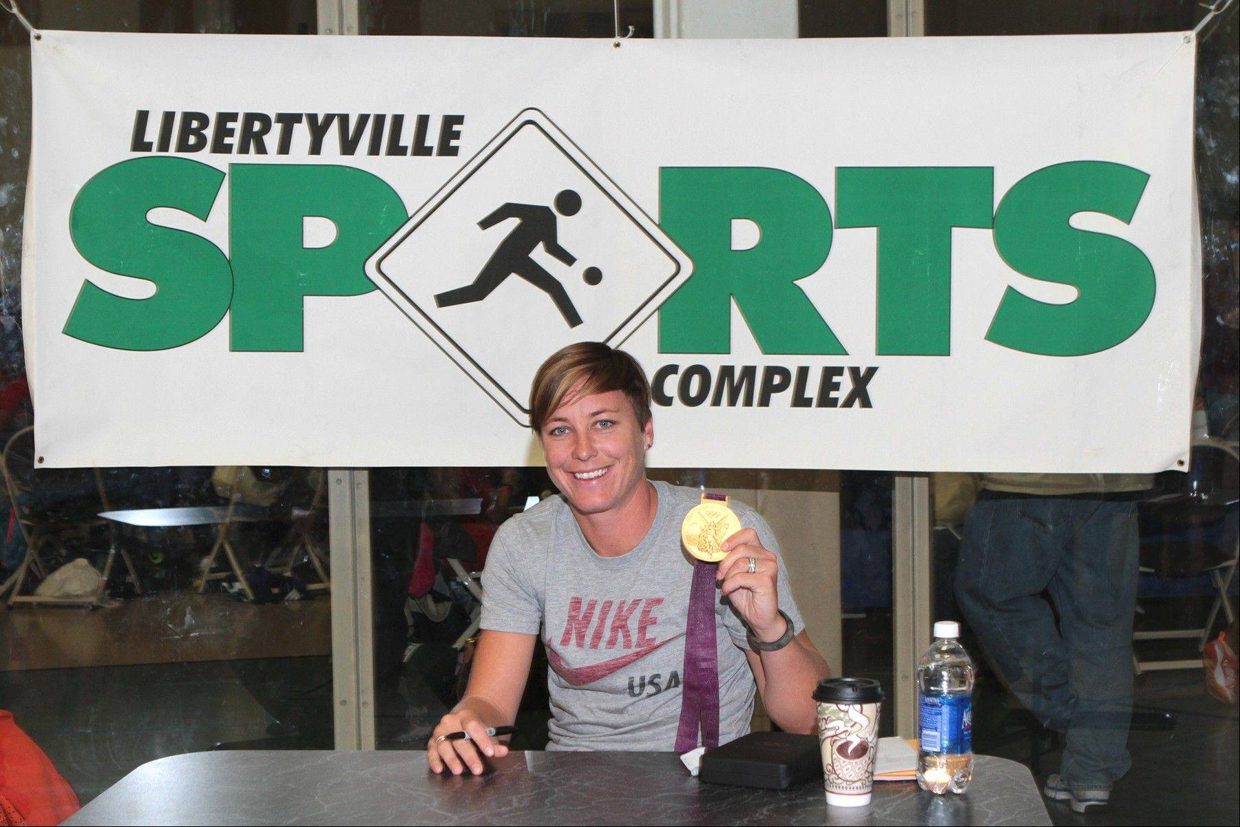 Team USA women's soccer star Abby Wambach displays her Olympic gold medal at the Libertyville Sports Complex last Saturday during the IYSA Soccer for Success event at the Libertyville Sports Complex.