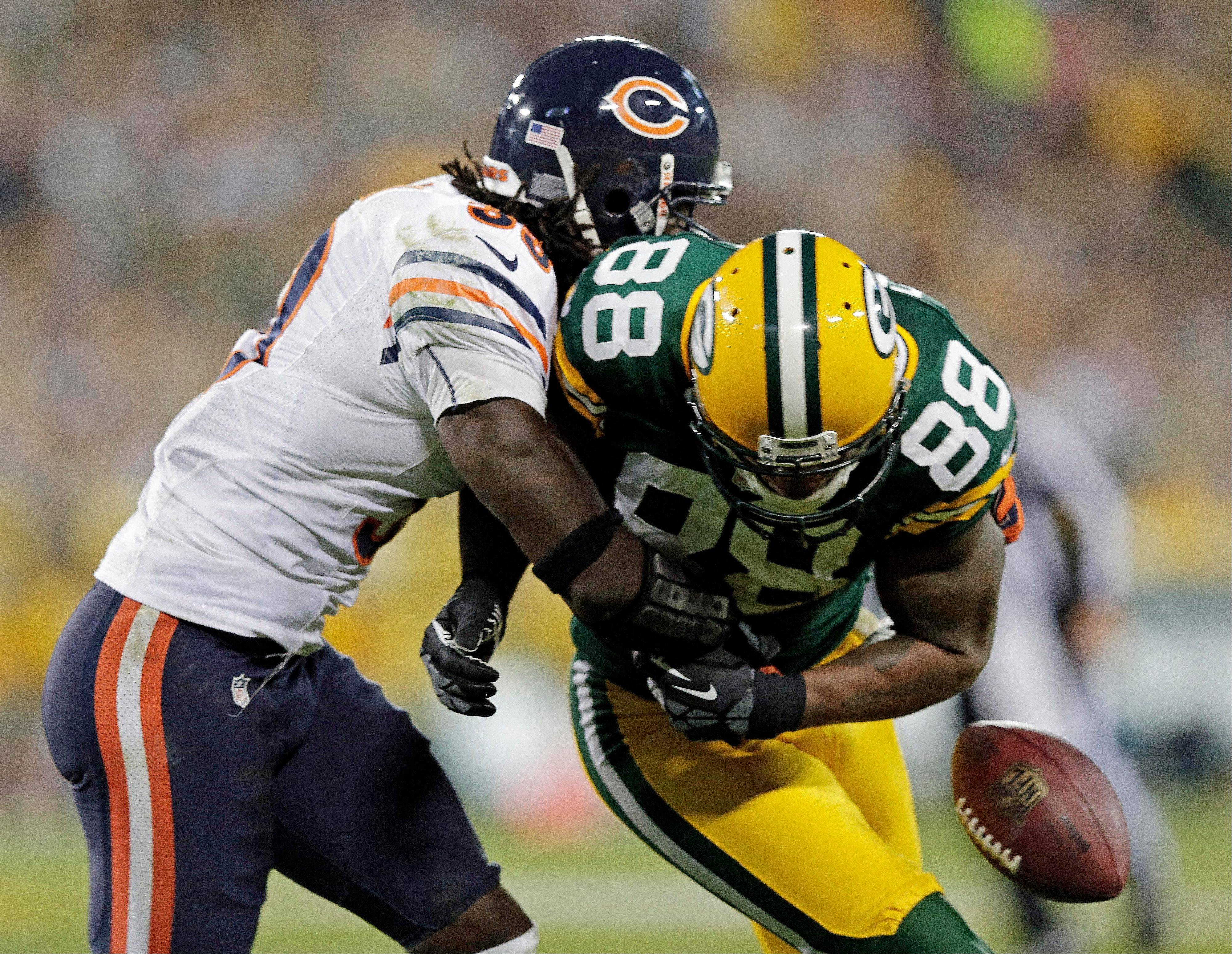 Green Bay's Jermichael Finley (88) fumbles as he is hit by Chicago Bears' Charles Tillman (33) during the second half of an NFL football game Thursday, Sept. 13, 2012, in Green Bay, Wis. The Bears recovered the fumble.