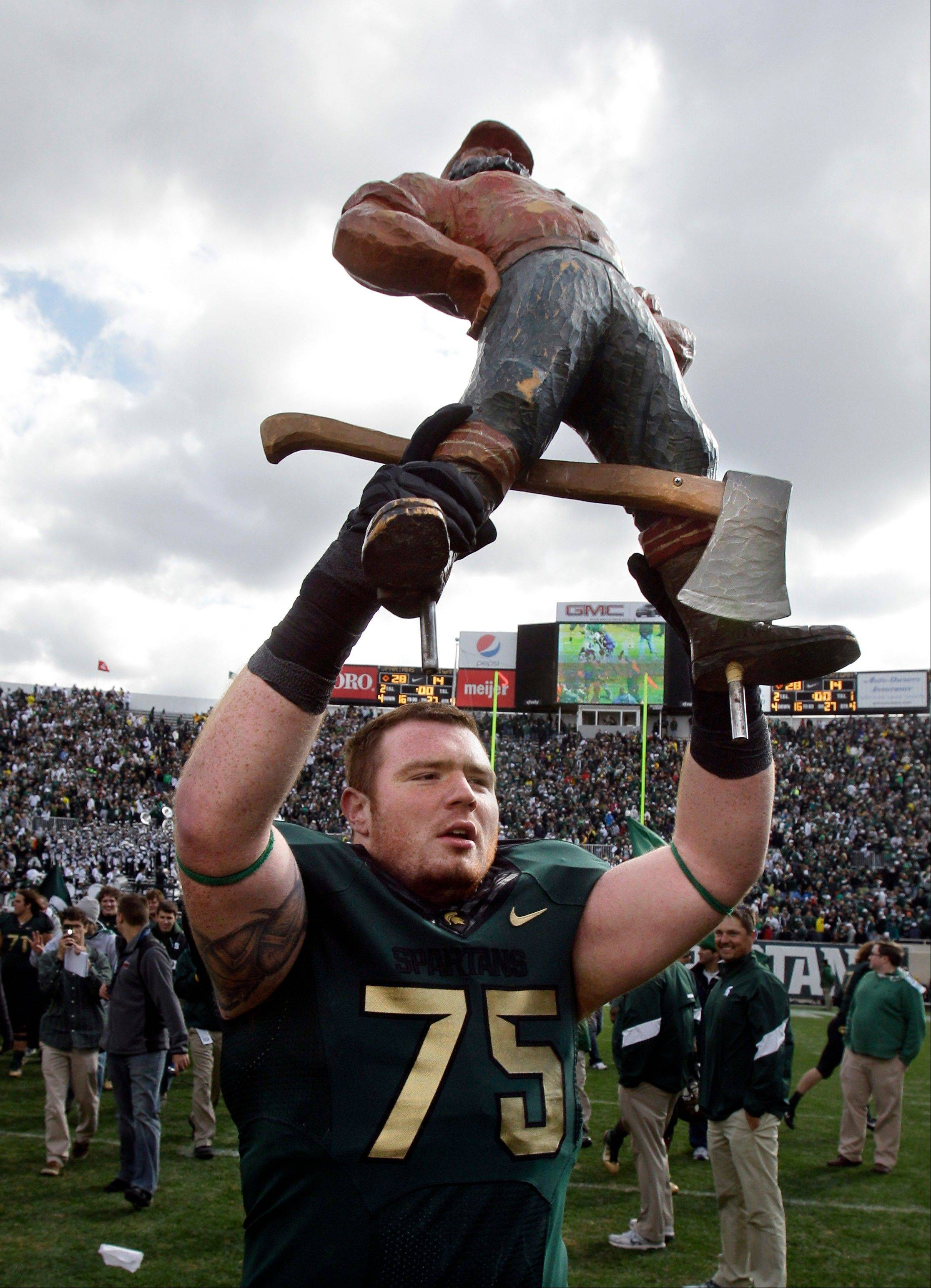 Michigan State offensive tackle Jared McGaha holds the Paul Bunyan Trophy after the Spartans defeated Michigan 28-14 last season in East Lansing, Mich.
