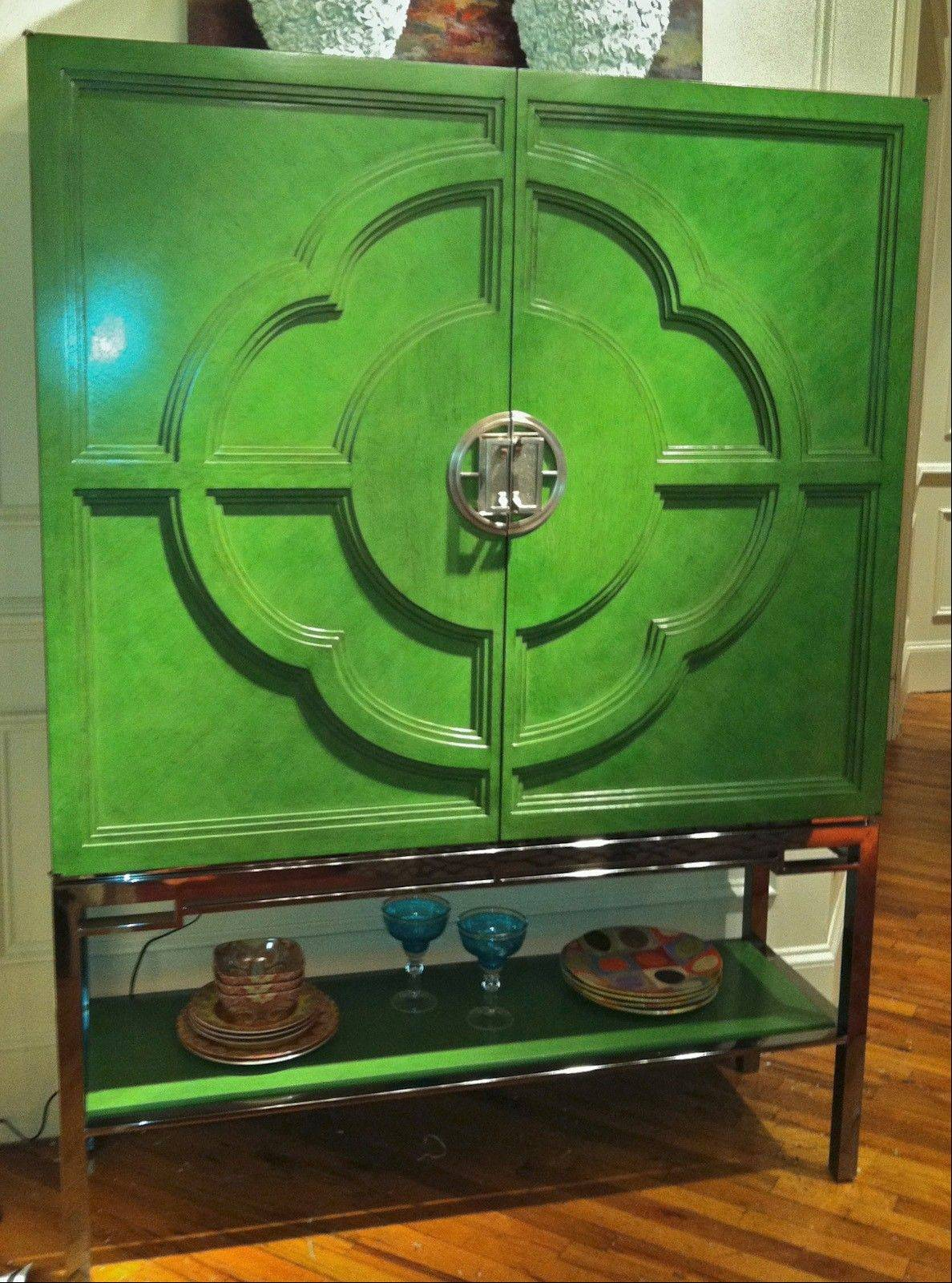 Painted lacquer in leaf-green highlights Century Furniture�s Chin Hua bar cabinet, which sits atop a stainless-steel base.