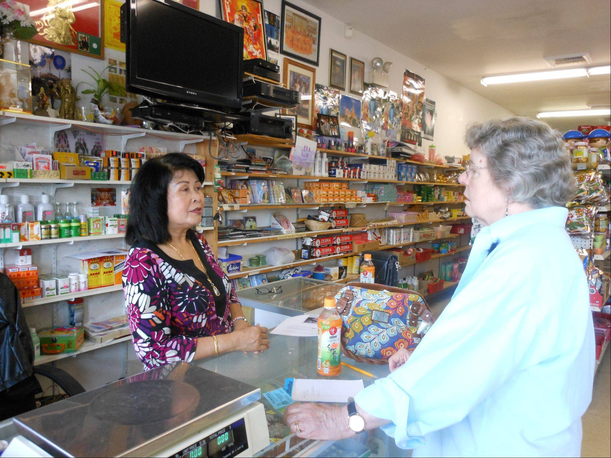 Baymone Rasavong chats with Shirley Anderson of Geneva at the B & V Asian Market in South Elgin.