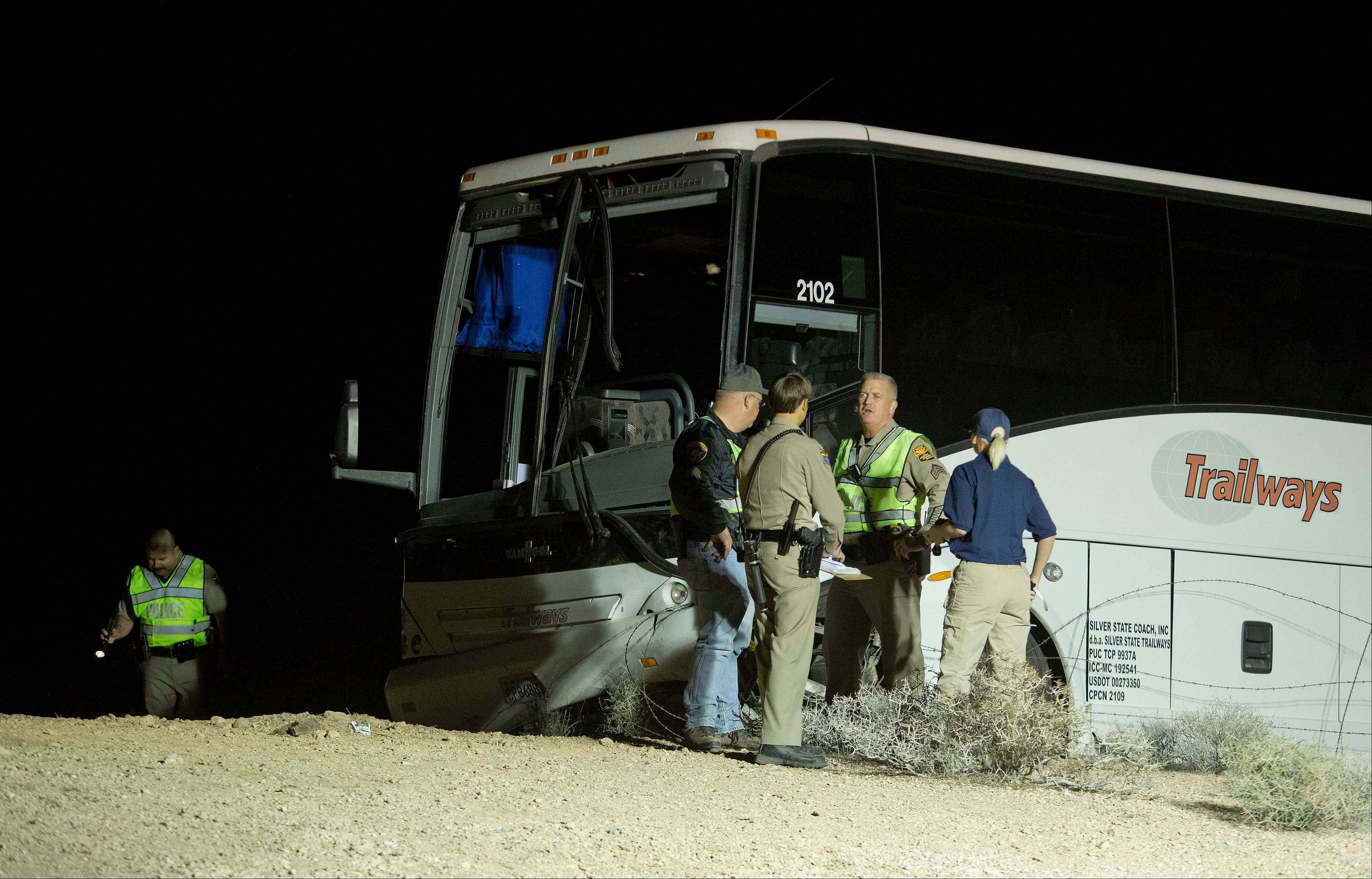 Arizona Highway Patrol officers examine the exterior of a tour bus that careened off the highway and crashed off northbound Highway 93, Friday, Oct. 19, near Willow Beach, Ariz. The crash killed the driver and left at least four passengers with serious injuries.