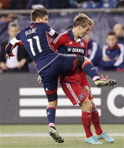 New England Revolution midfielder Kelyn Rowe knees Chicago Fire forward Chris Rolfe during their MLS soccer match in Foxborough, Mass., Saturday. The Revolution won 1-0.