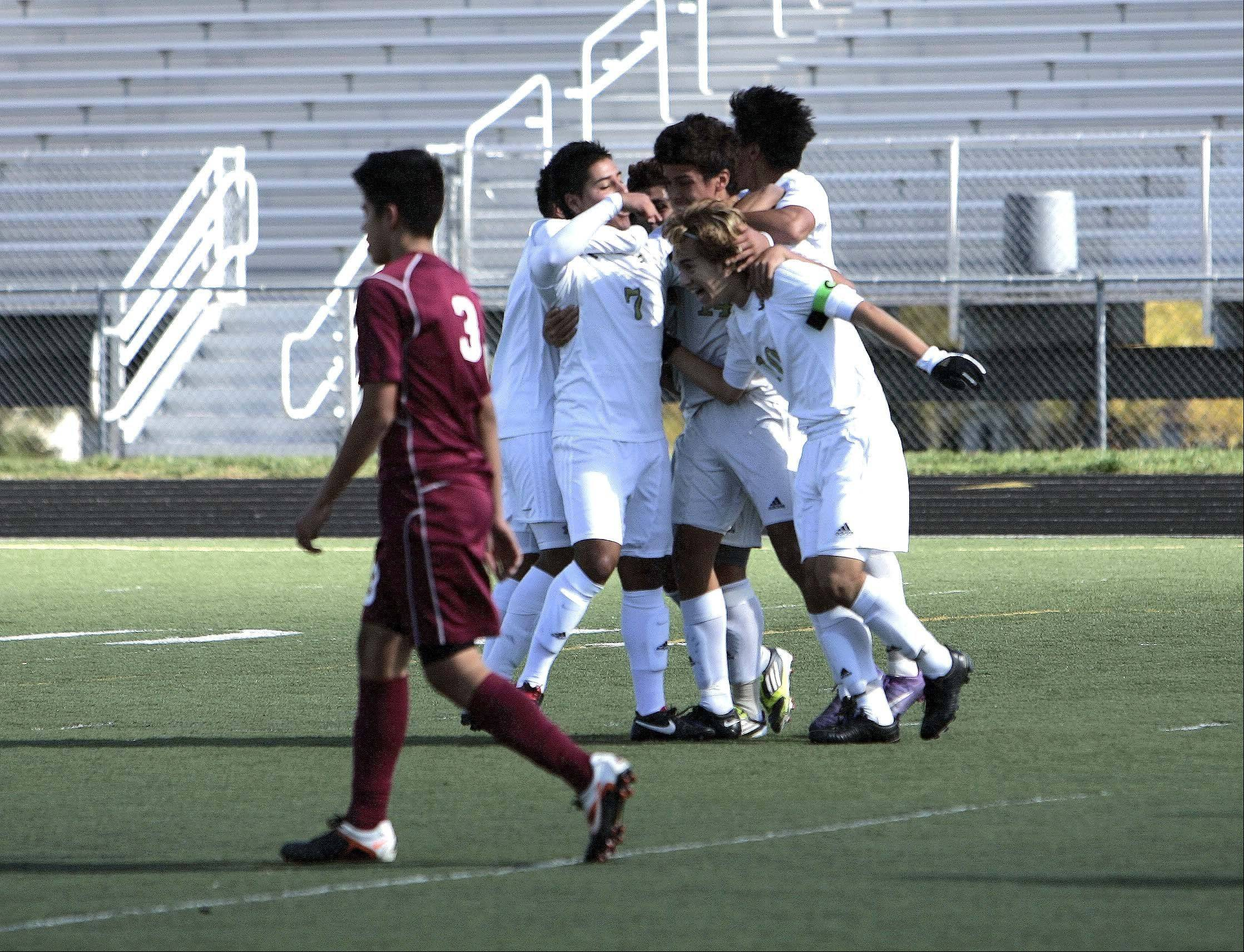 Streamwood's Nestor Ascencio is mobbed by his team after scoring a goal during the Sabres' 5-0 regional final win over Elgin Saturday at Millennium Field.