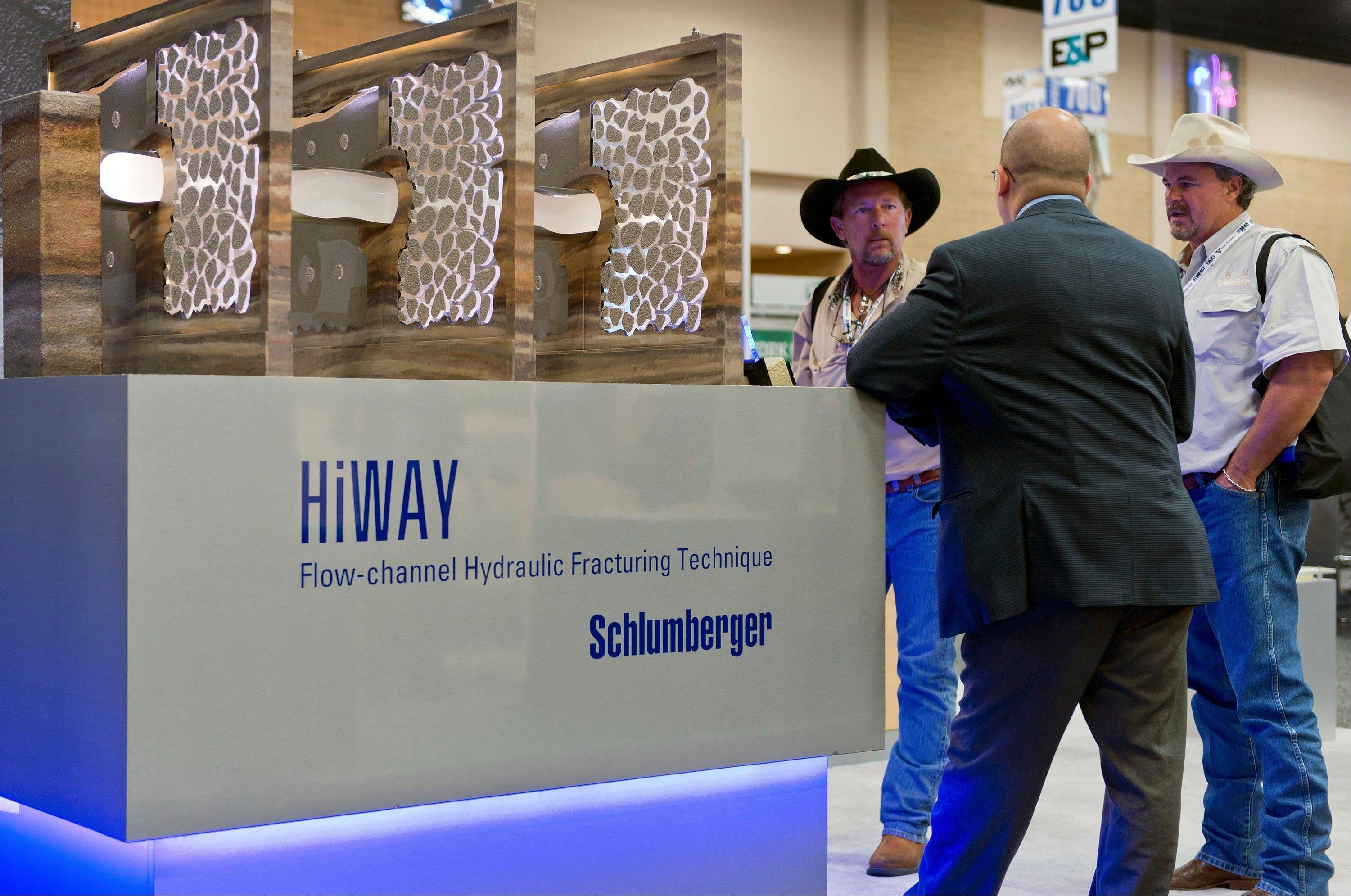 A Schlumberger Ltd. representative, center, discusses the company's HiWAY Flow Channel Hydraulic Fracturing system last Monday with attendees at the DUG Eagle Ford Conference & Exhibition in San Antonio, Texas.