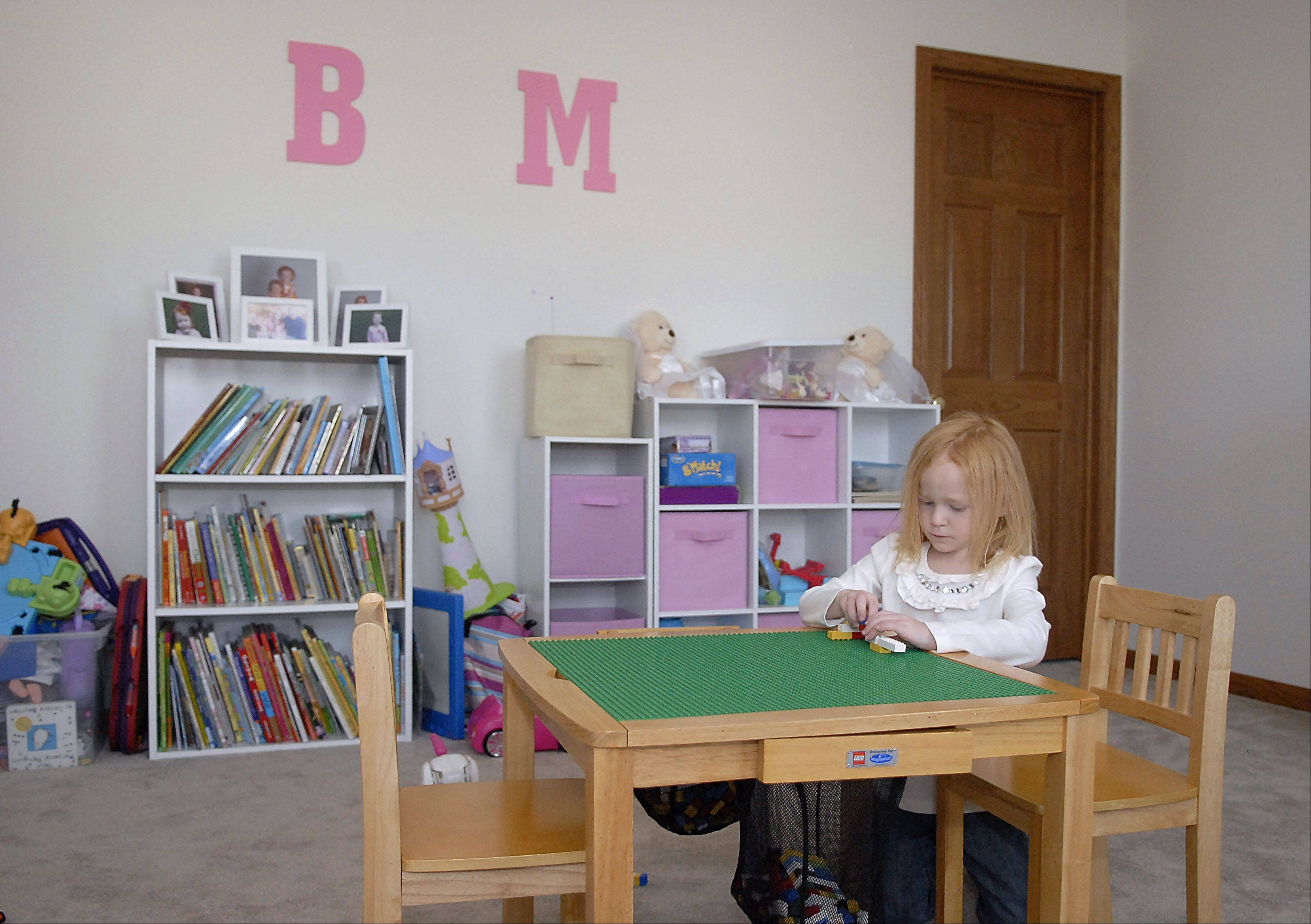 Madison Waller, 4, plays in an upstairs playroom she shares with sister Brooke in the family's new Pingree Grove home. The large playroom was a big plus for parents Kari and Todd Waller in selecting the house.