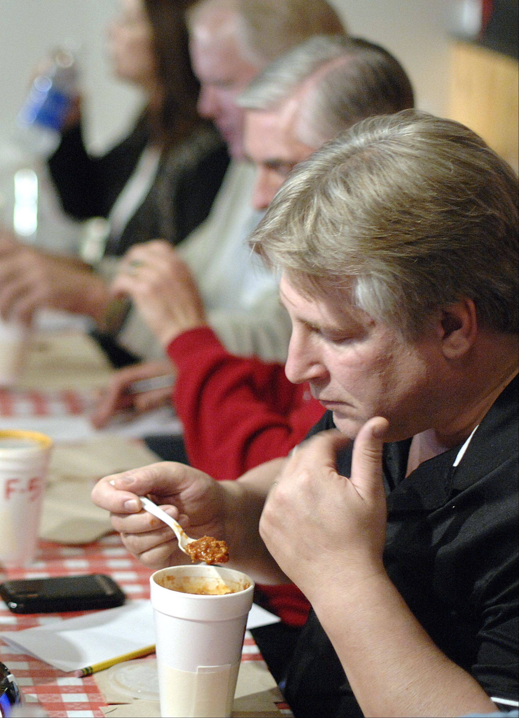 Scott Henry of Wheaton enjoys the aroma of a cup of chili before judging it at Kuipers Family Farm's third annual Chili Cook-Off in Maple Park on Saturday. All proceeds of the competition go to Conley Outreach Community Services in Elburn.