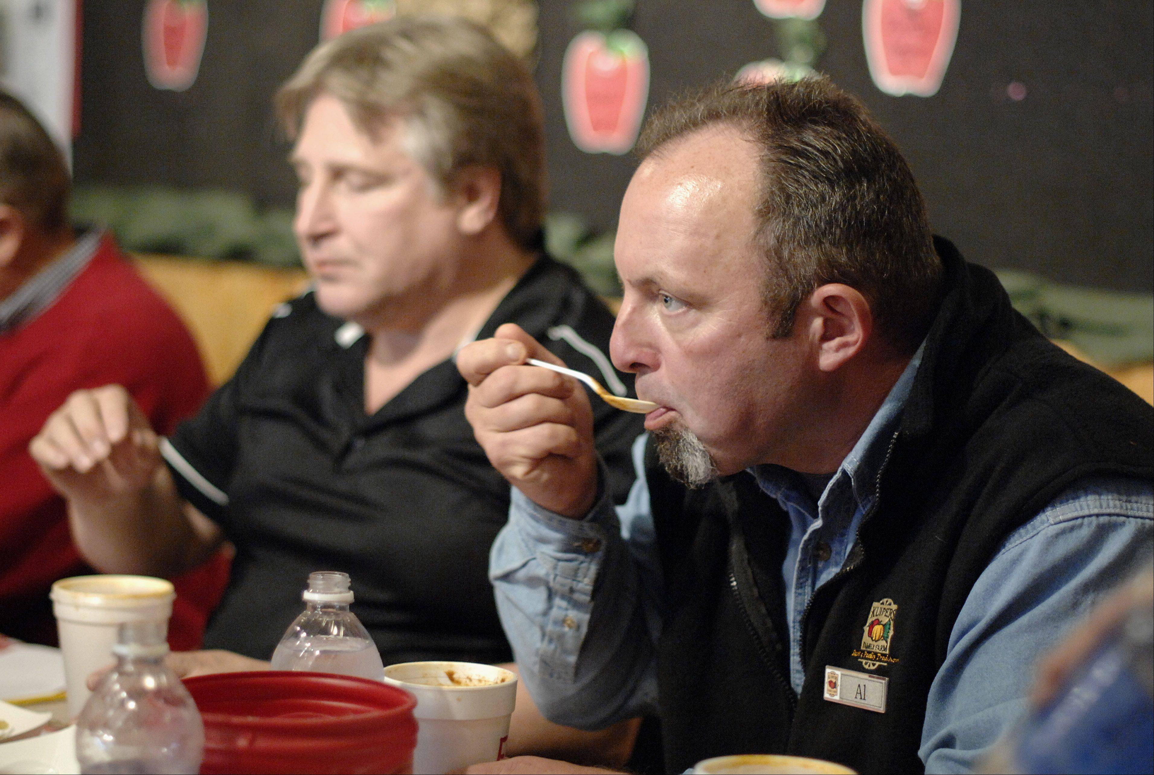 Al Shelton, food and beverage manager for Kuipers Family Farm, samples chili during judging at the farm's third annual Chili Cook-Off in Maple Park on Saturday.