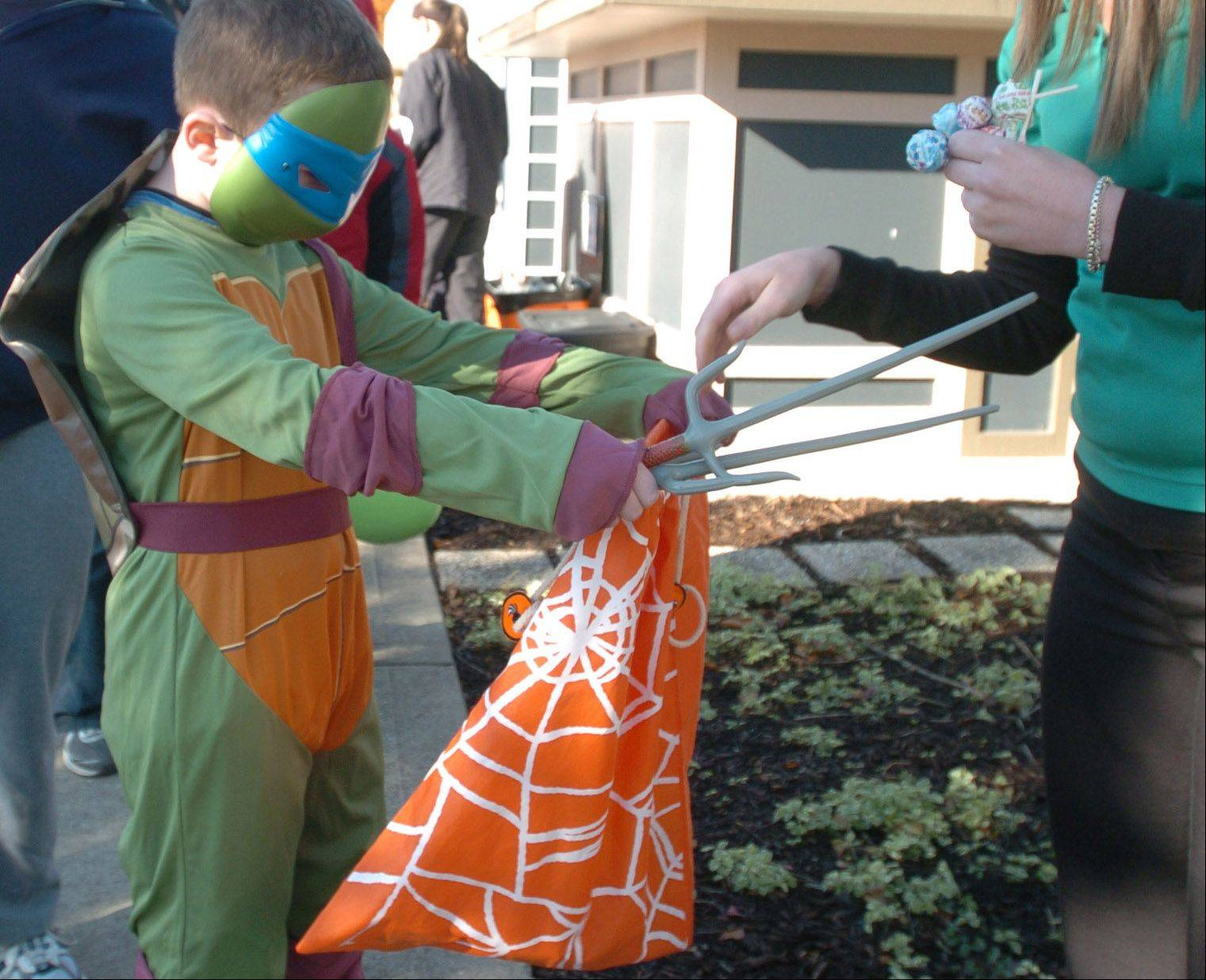 Dressed as a turtle, Aiden Spenner, 8, of Naperville gets candy from a volunteer during the annual Trick or Treat at Safety Town in Naperville Saturday.