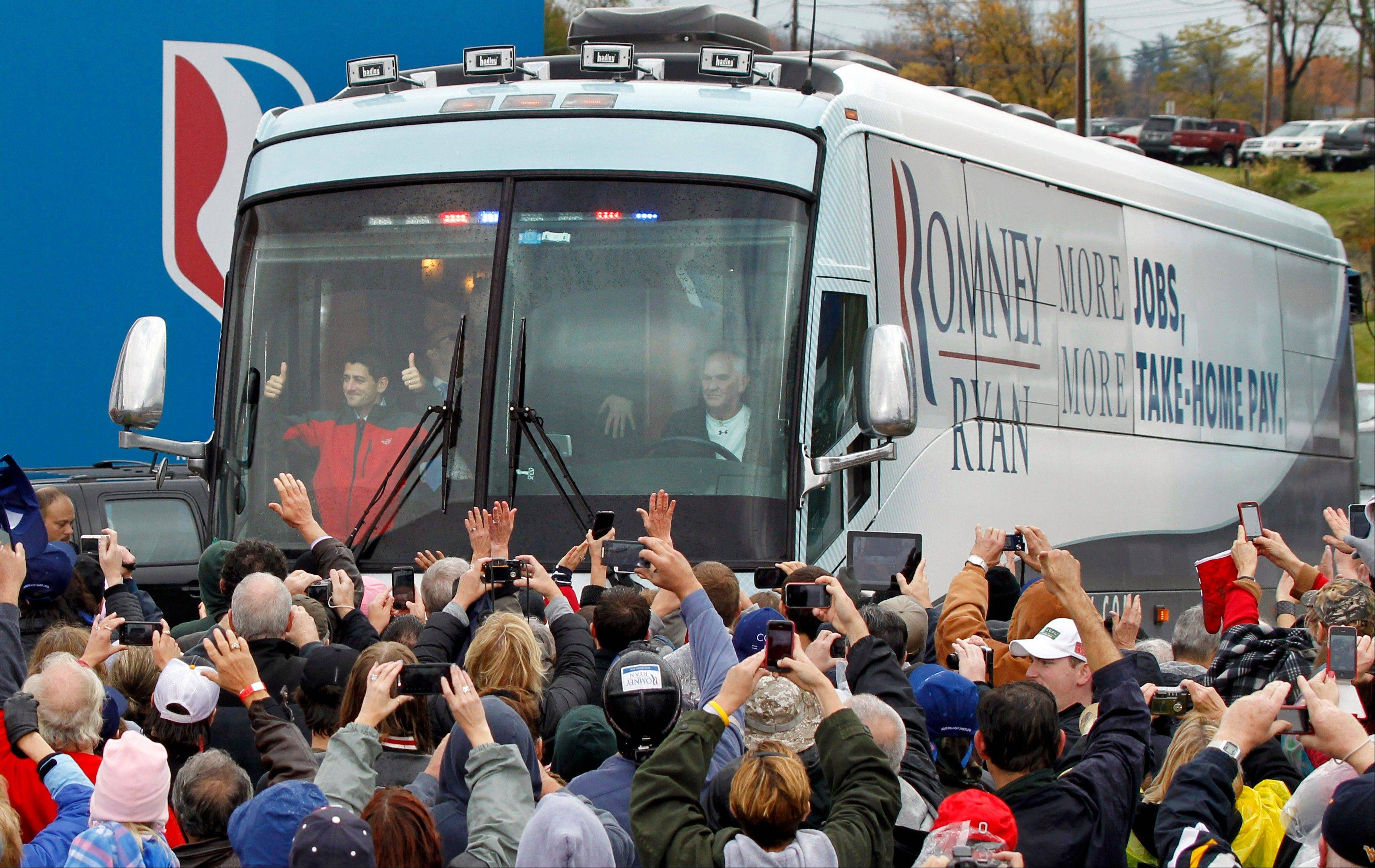 Republican vice presidential candidate, Wisconsin Rep. Paul Ryan, left in front of bus, gives a thumbs-up to supporters as he arrives Saturday for a campaign rally at the Valley View Campgrounds in Belmont, Ohio.