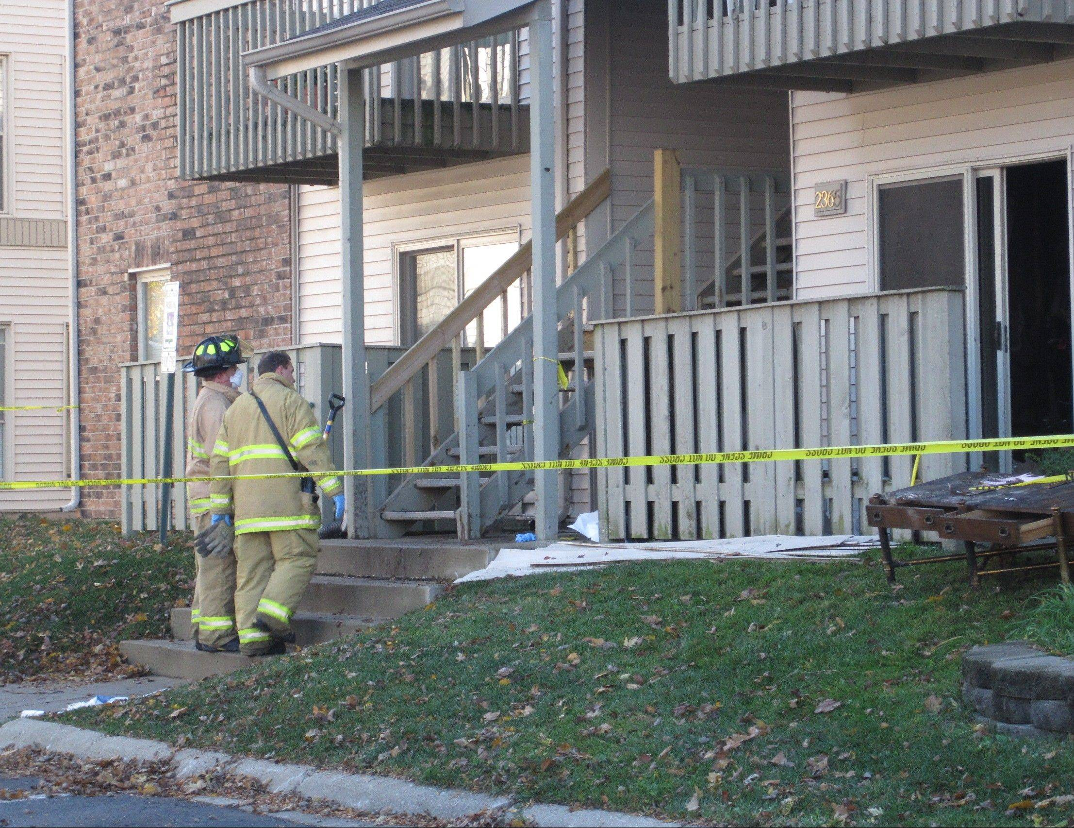 Members of the Mount Prospect Fire Department Saturday morning are outside a first-floor unit at The Colony Apartments on the 2300 block of South Cannon Drive, where a 69-year-old woman died after a fire early Saturday.