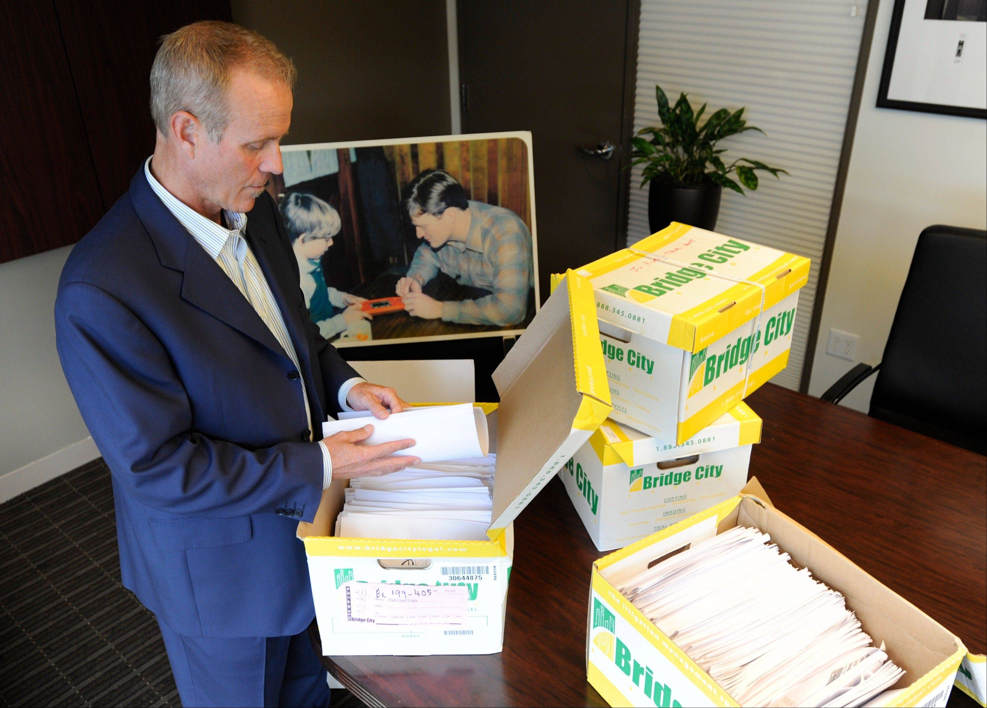 Portland attorney Kelly Clark examines some of the 14,500 pages of previously confidential documents created by the Boy Scouts of America concerning child sexual abuse within the organization Tuesday in preparation for releasing the documents Thursday as he stands in his office in Portland, Ore. The Boy Scouts of America fought to keep those files confidential.