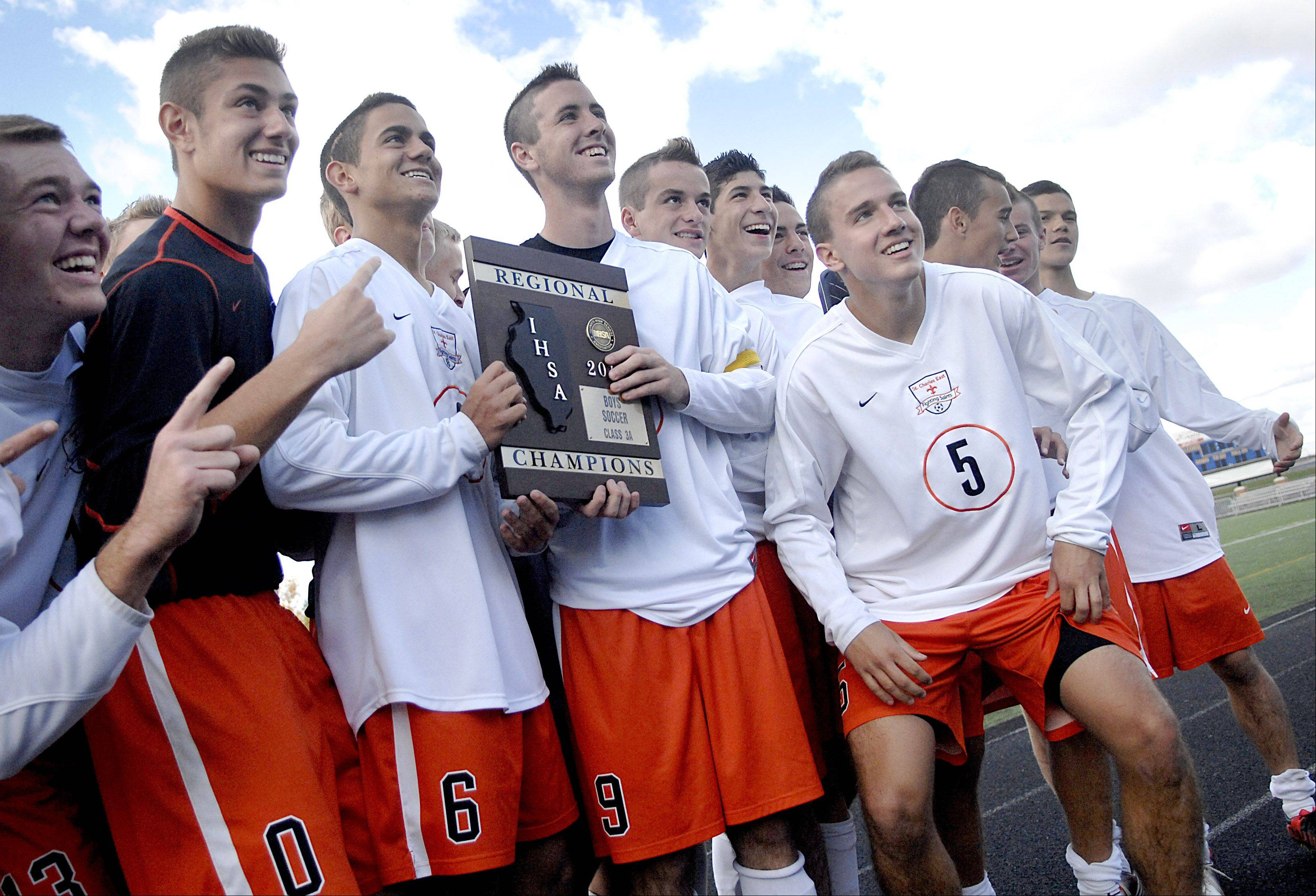 St. Charles East's Michael Macek and Brian Gielow show the Saints' regional plaque to their fans on Saturday, October 20.