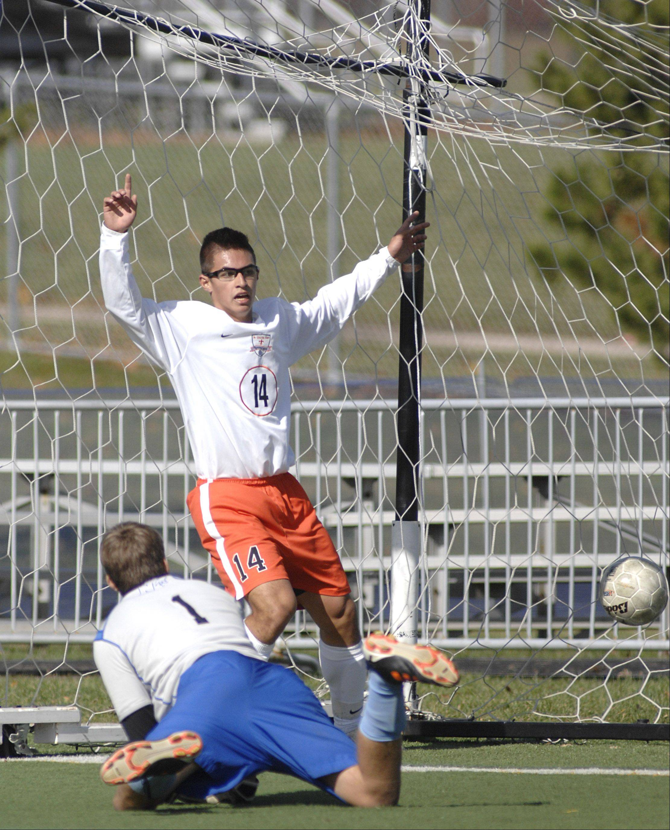 St. Charles East's Zach Manibog celebrates the goal made by teammate Andrew Shone across the field before St. Charles North goalie Hansen Hagemann even hits the ground in the final seconds of the first half on Saturday, October 20.