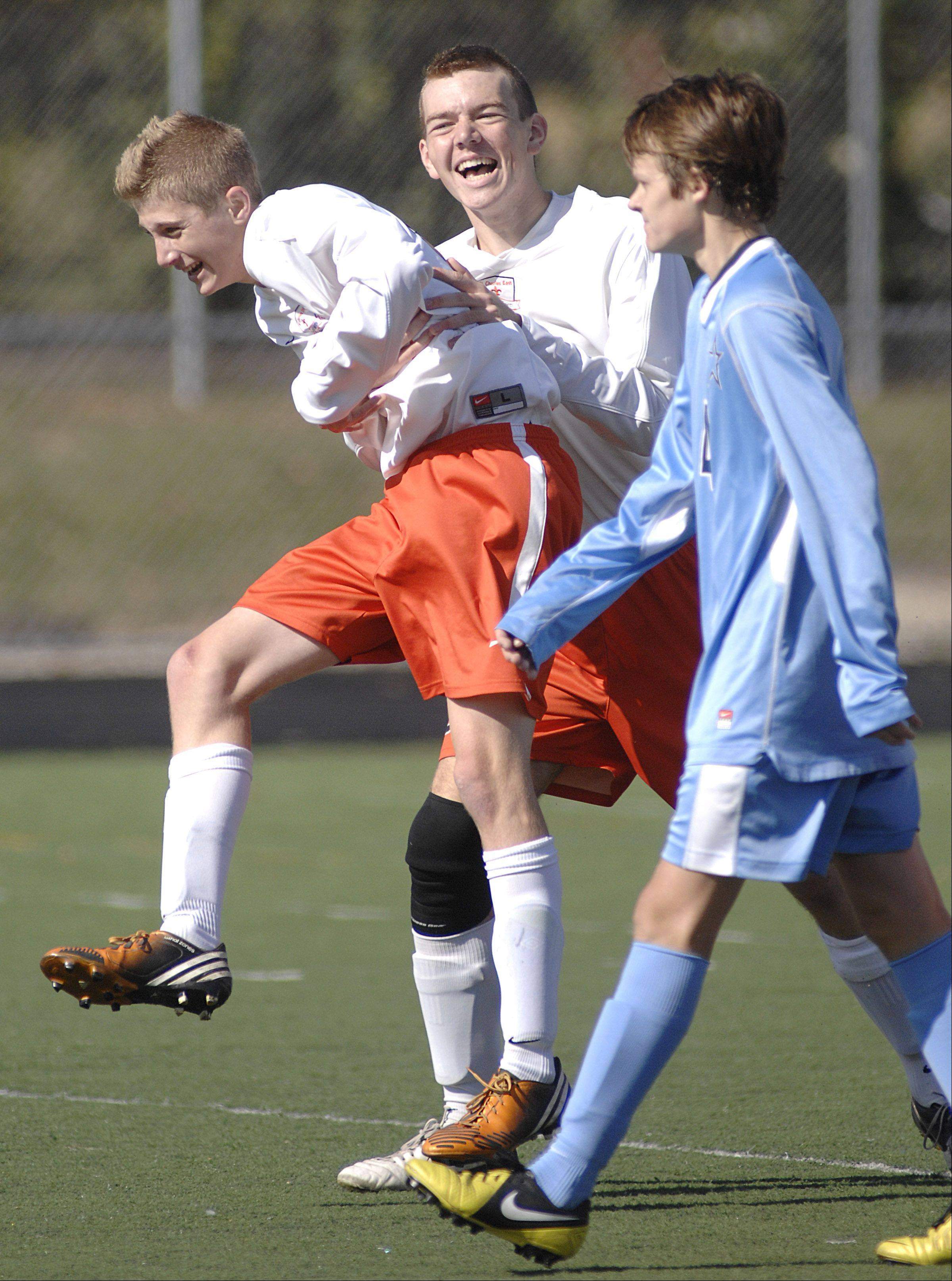 St. Charles East's Andrew Shone, left, gets lifted in a hug from teammate Brandon Villanueva after scoring a goal in the final seconds of the first half of the regional championship on Saturday, October 20.