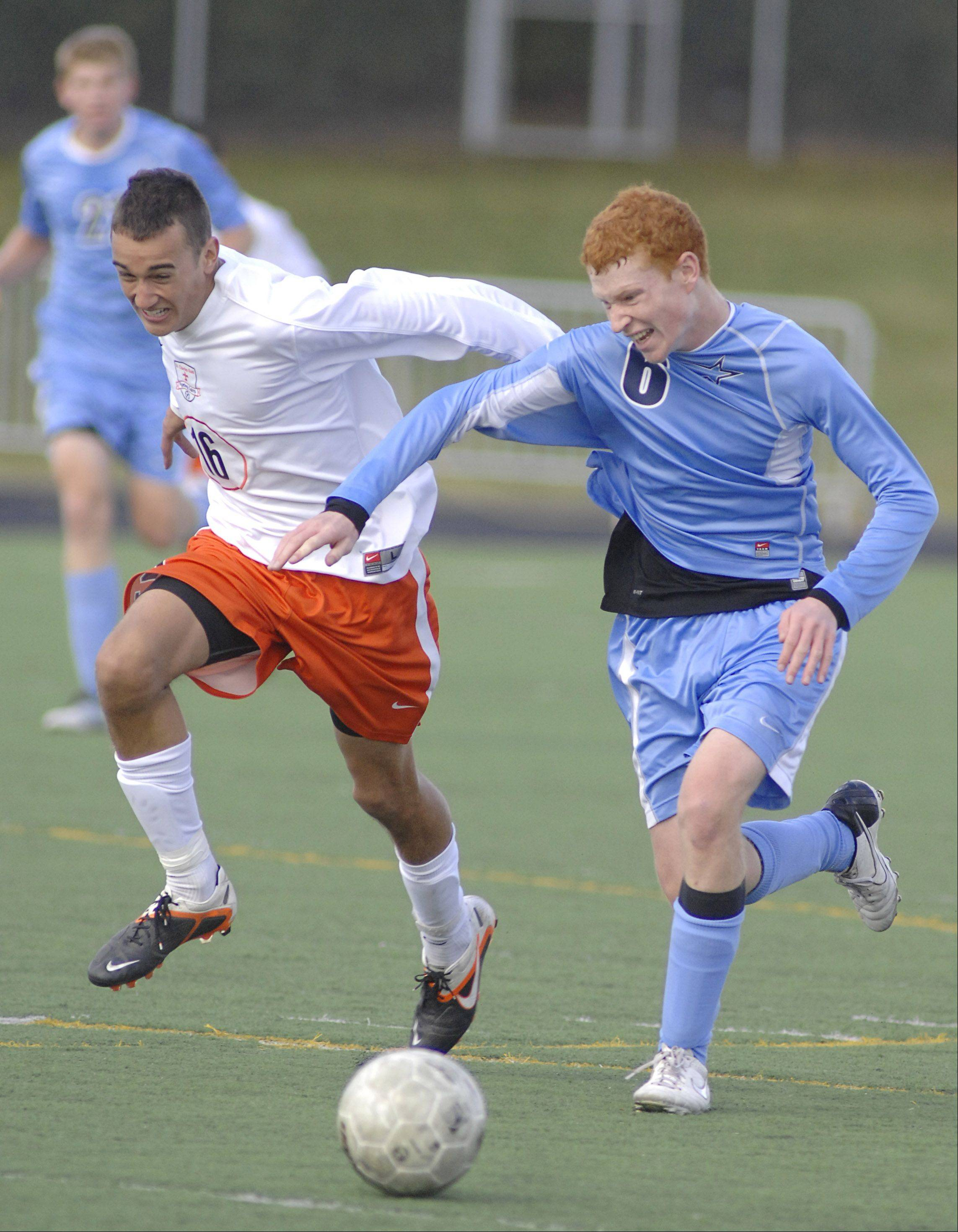 St. Charles East's Jordan Moore and St. Charles North's Jack Fries battle for the ball in the second half of the regional championship on Saturday, October 20.