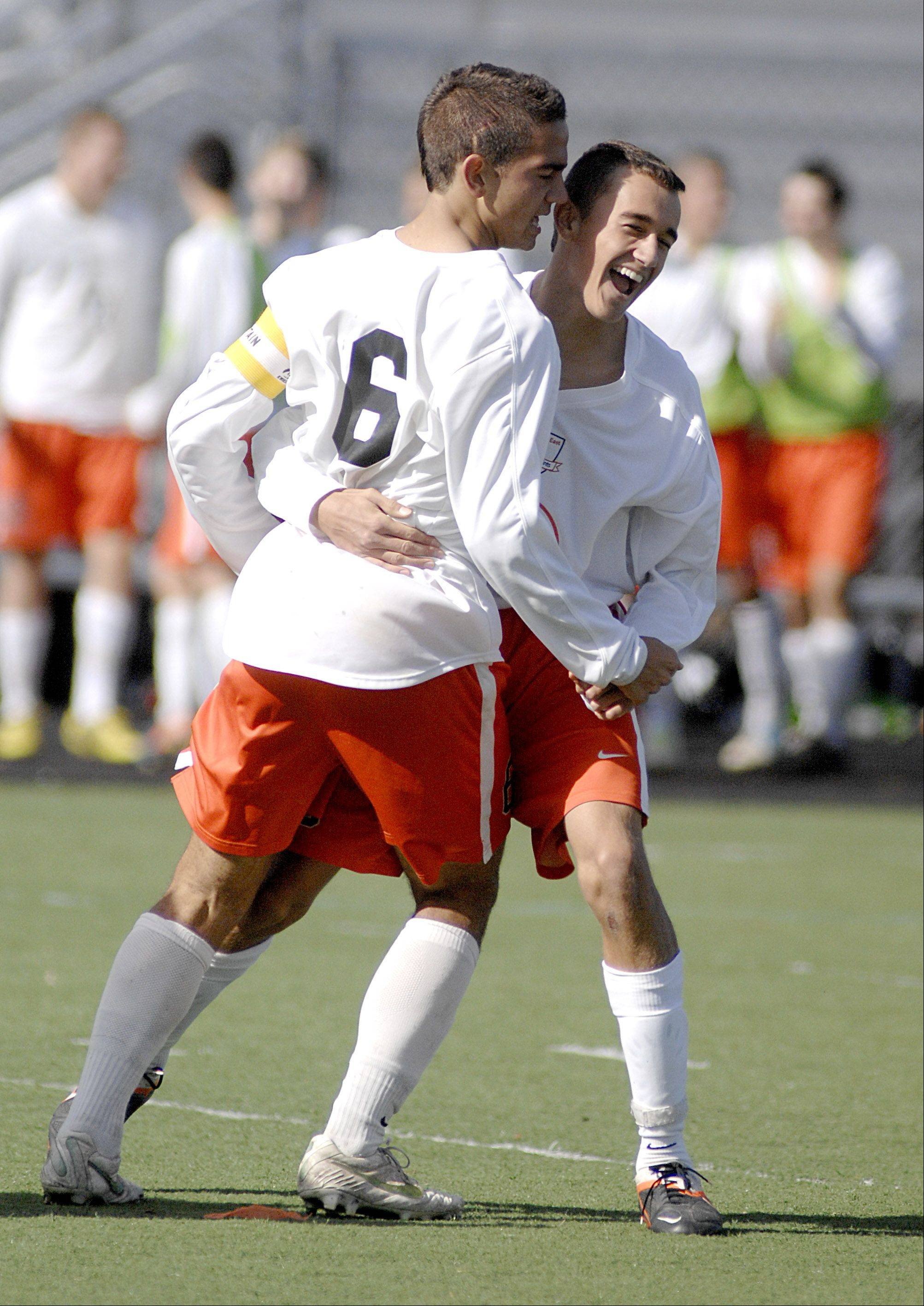 St. Charles East's Michael Macek, left, gets a hug from teammate Jordan Moore after Macek scored a goal in the second half on Saturday, October 20.