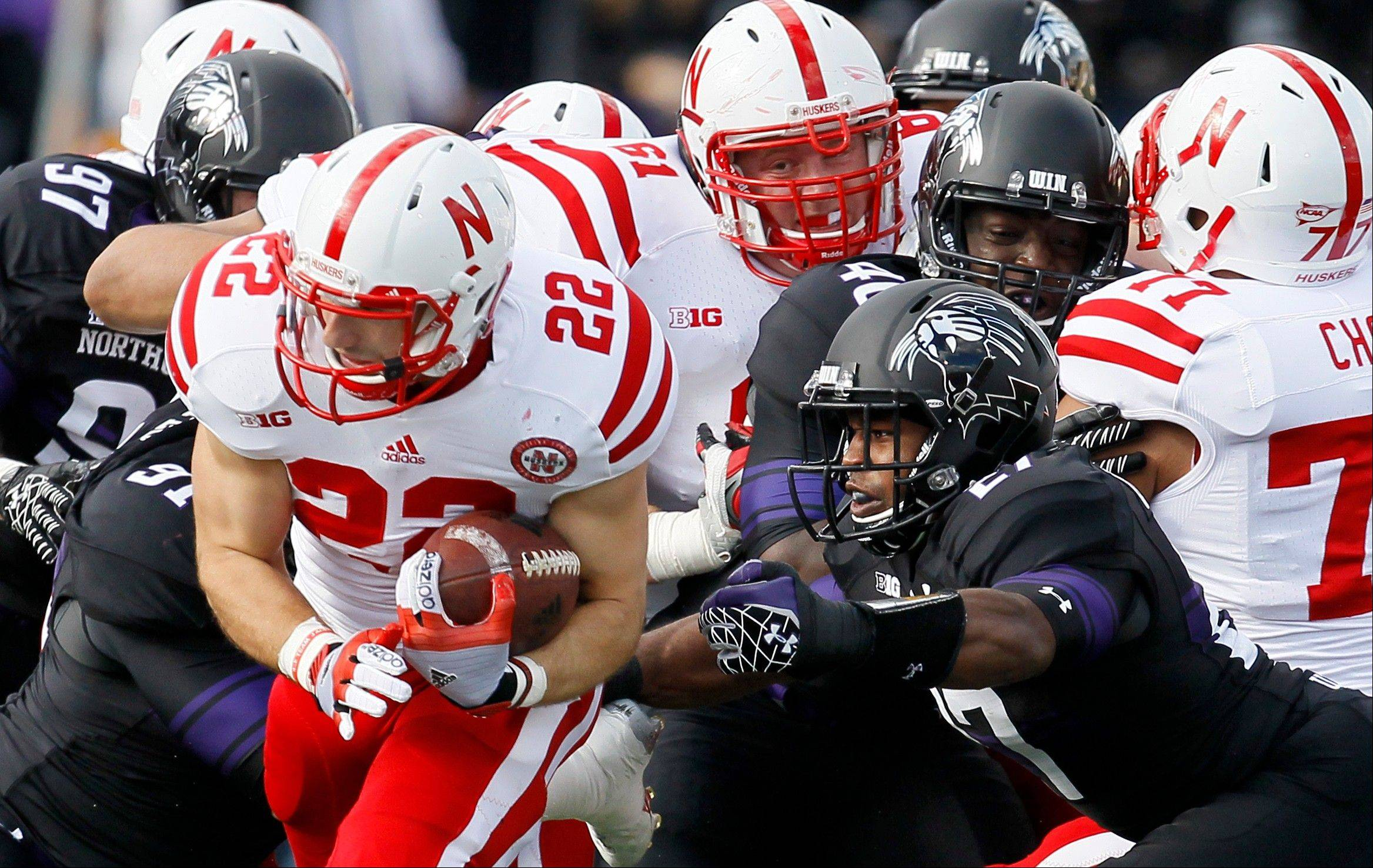 Nebraska running back Rex Burkhead (22) carries the ball past Northwestern safety Jared Carpenter (27) during the first half of an NCAA college football game on Saturday, Oct. 20, 2012, in Evanston.