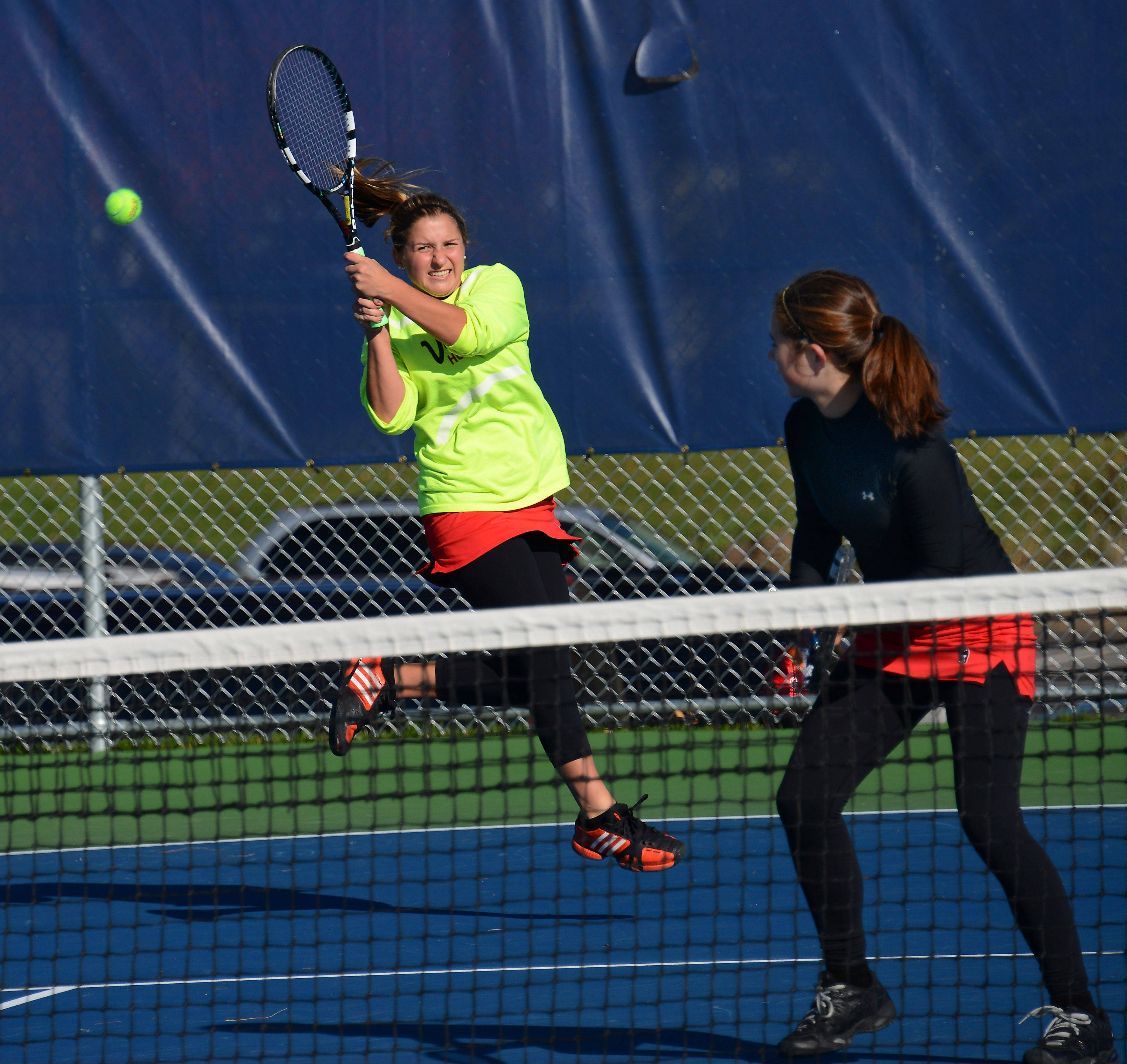 Hinsdale Central's Caroline Lorenzini returns a serve while doubles partner Marika Cusick looks on at Buffalo Grove on Saturday.