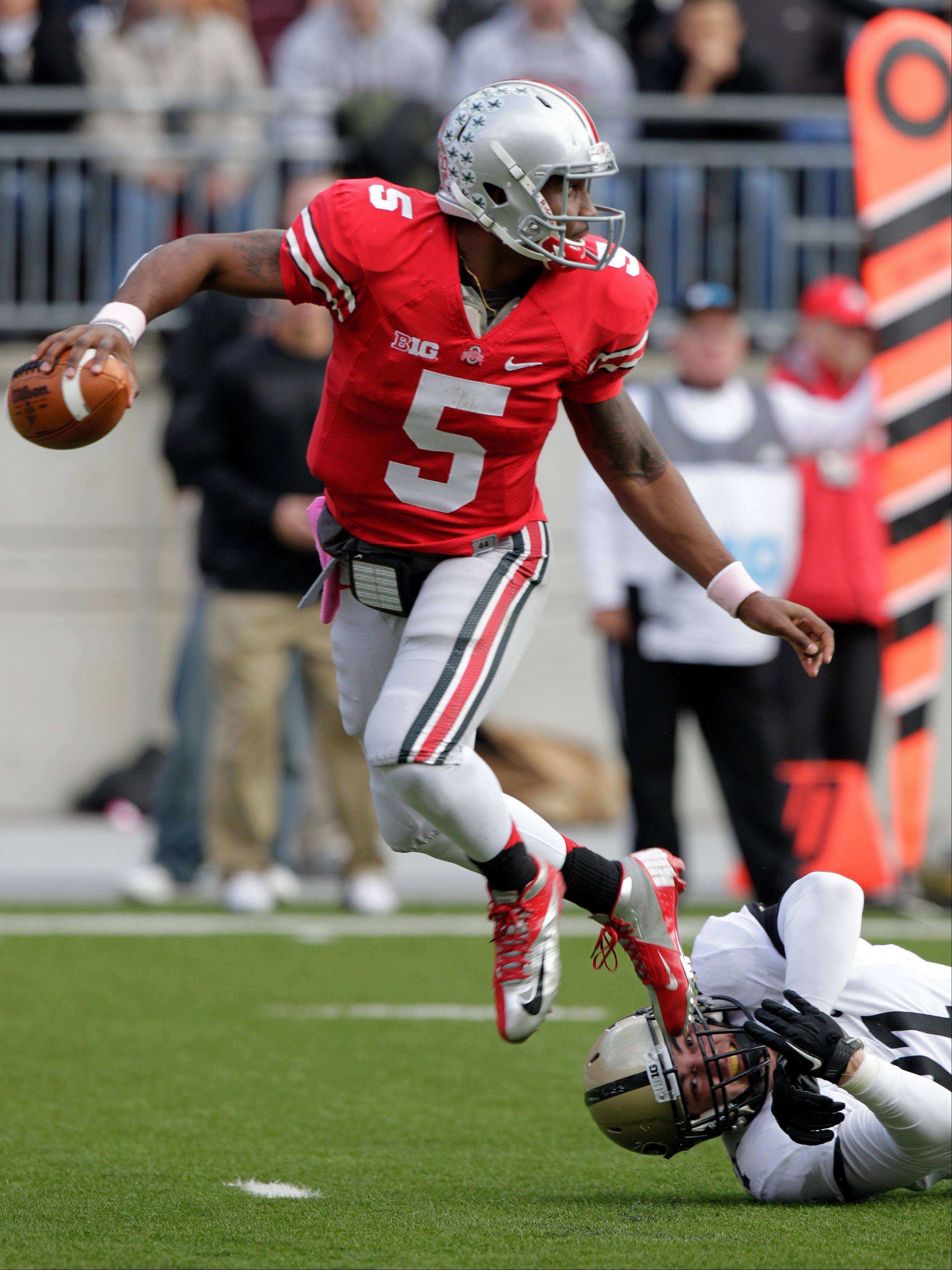 Ohio State quarterback Braxton Miller, left, escapes the grasp of Purdue defensive end Greg Latta during the second quarter of an NCAA college football game Saturday, Oct. 20, 2012, in Columbus, Ohio.