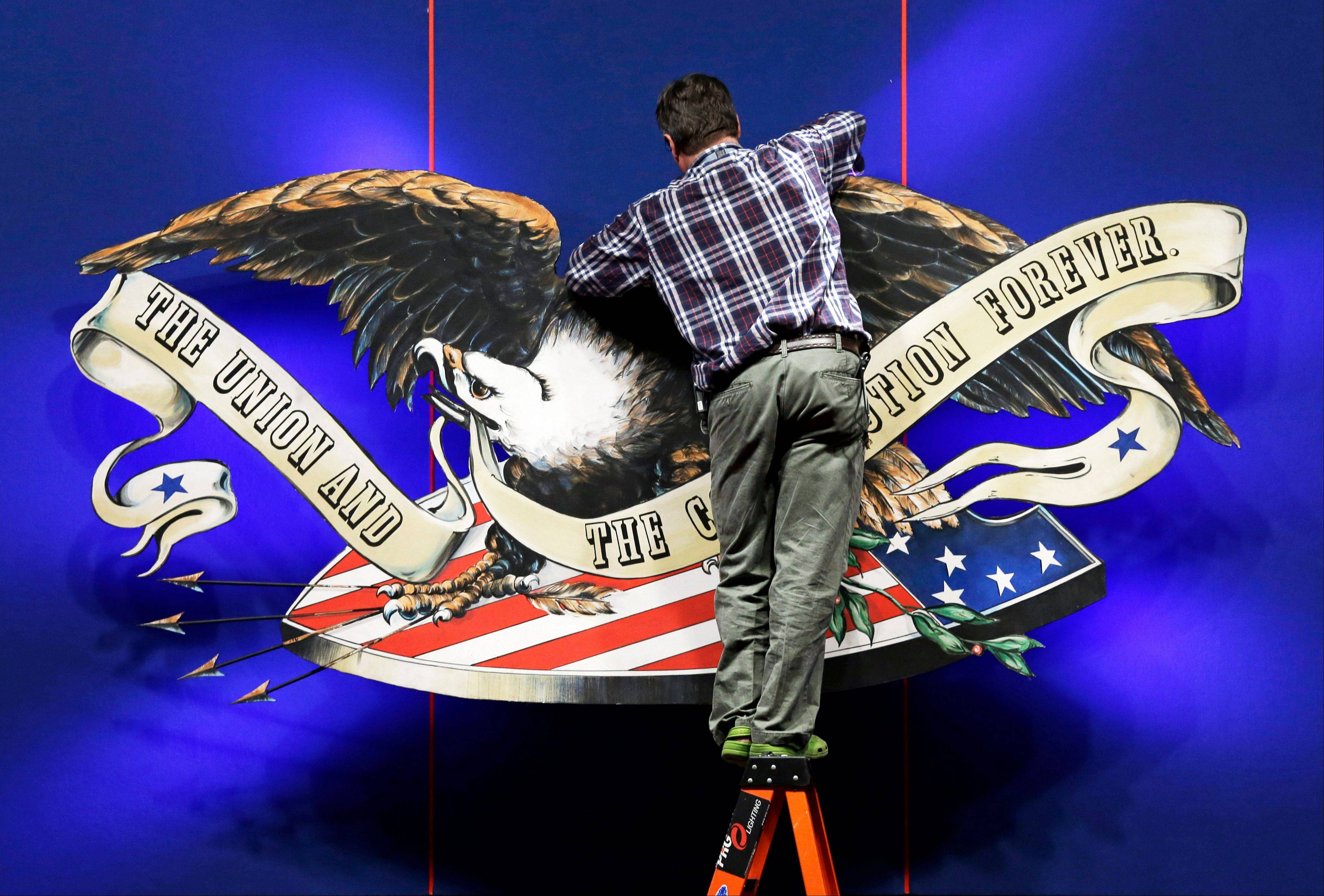 A worker adjusts the backdrop on stage in preparation for Monday's presidential debate between President Barack Obama and Republican presidential candidate, former Massachusetts Gov. Mitt Romney, Sunday at Lynn University in Boca Raton, Fla.