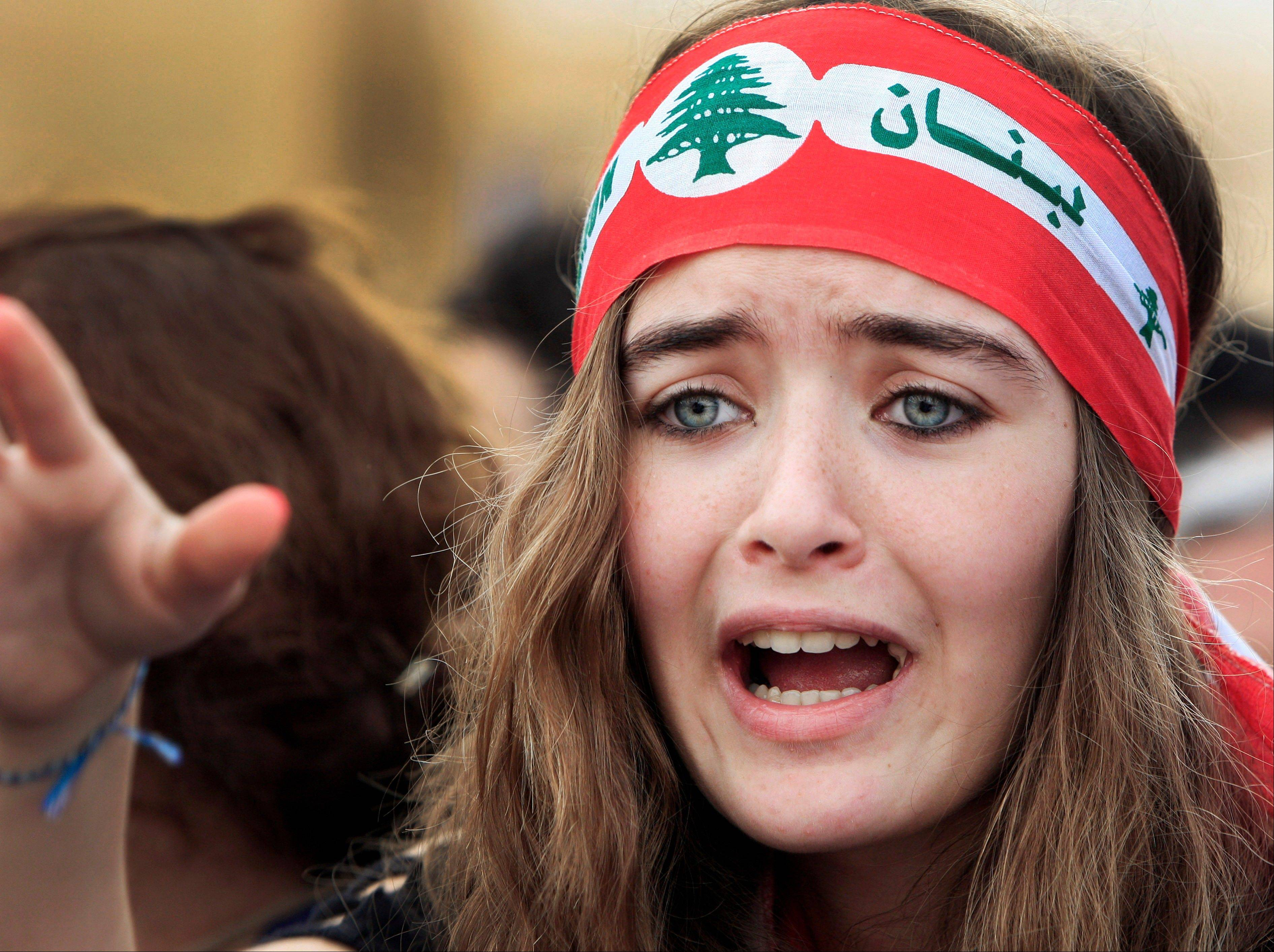 An anti-Syrian regime protester reacts in Martyrs' Square during the funeral for the country's intelligence chief, Brig. Gen. Wissam al-Hassan, in Beirut, Lebanon, Sunday. Lebanese soldiers fired guns and tear gas to push back hundreds of protesters who broke through a police cordon and tried to storm the government headquarters.