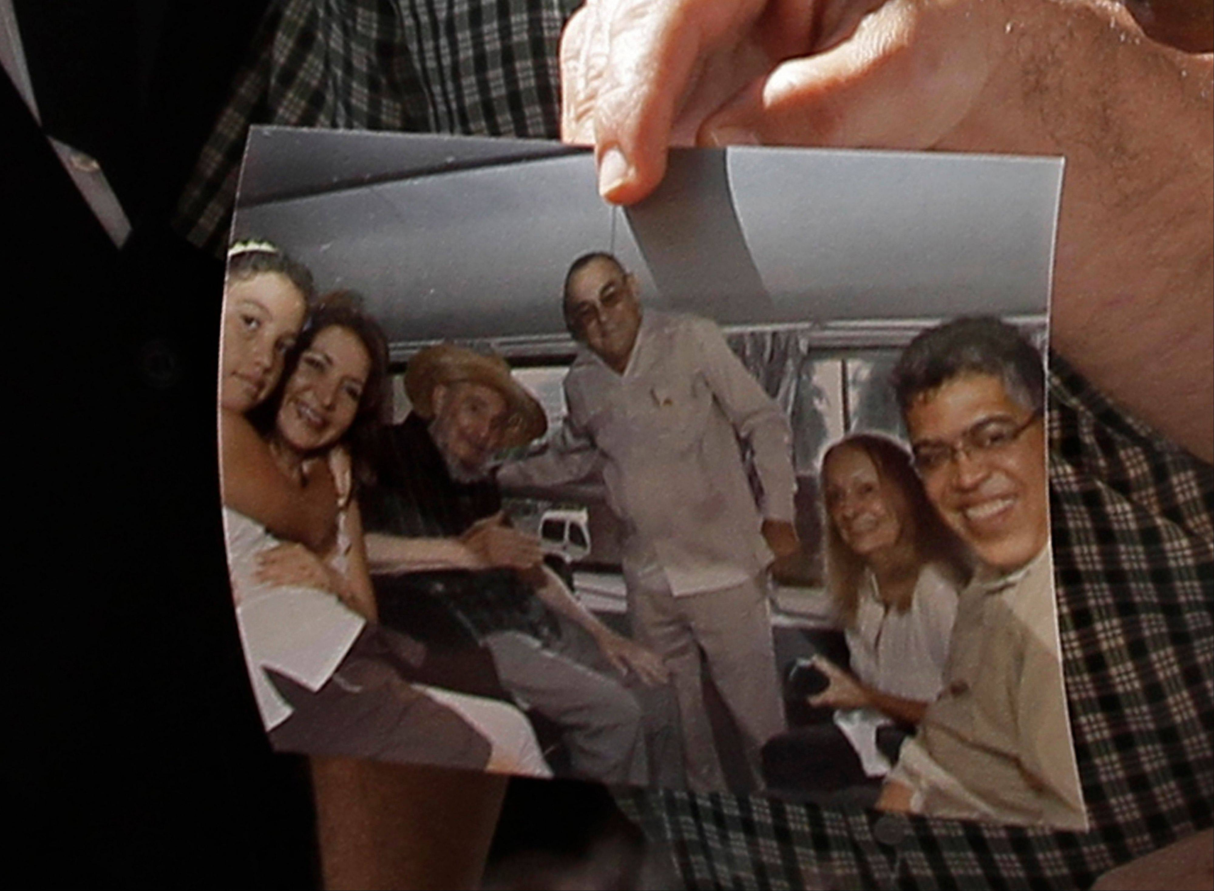 Former Venezuelan Vice President Elias Jaua shows a picture of Cuba's leader Fidel Castro, third from left, in Havana Sunday. According to Jaua, the picture was taken Saturday inside a van.