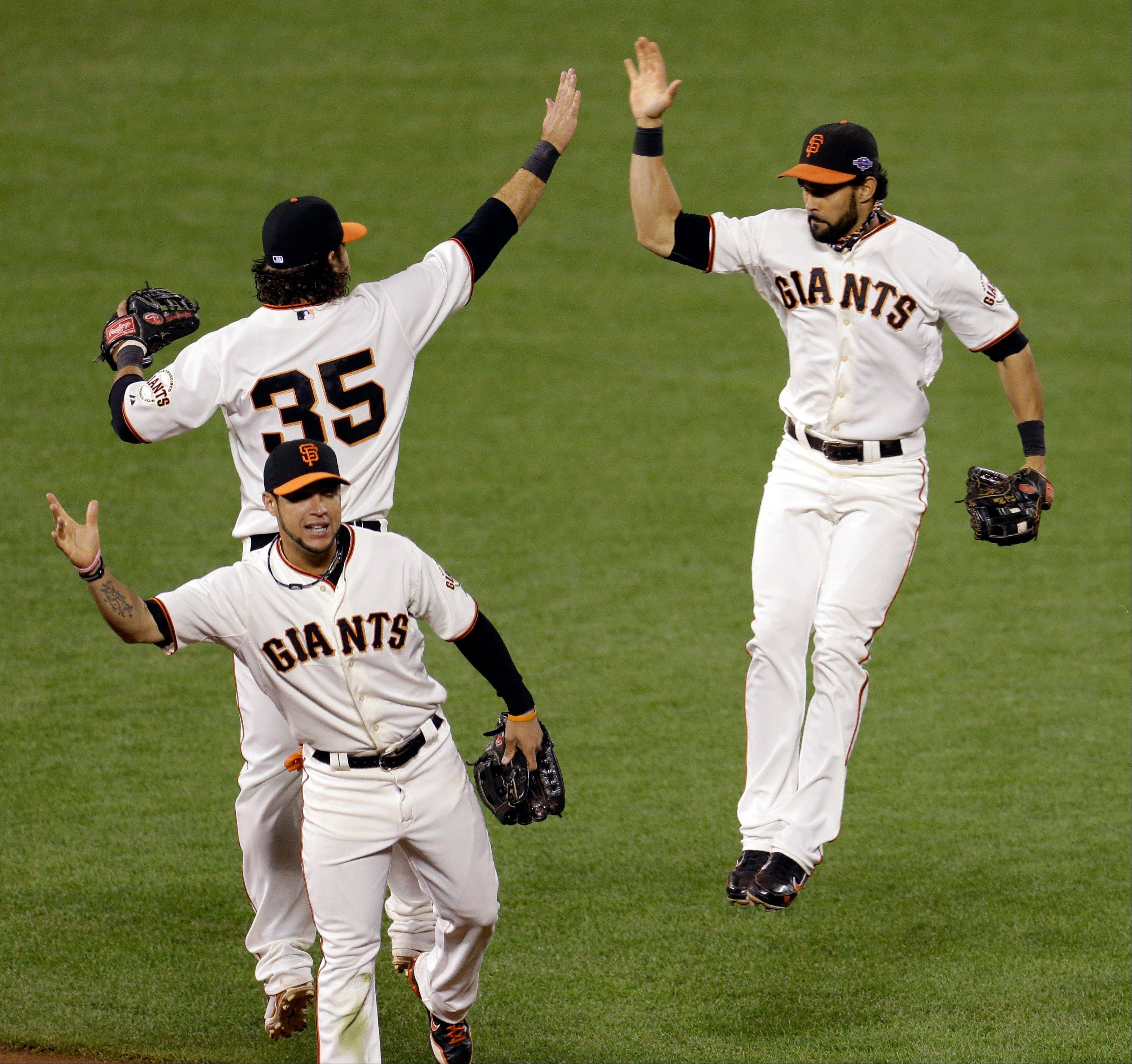 The Giants� Brandon Crawford (35), Angel Pagan, right, and Gregor Blanco celebrate winning after Game 6 of the National League championship series against the St. Louis Cardinals on Sunday in San Francisco.