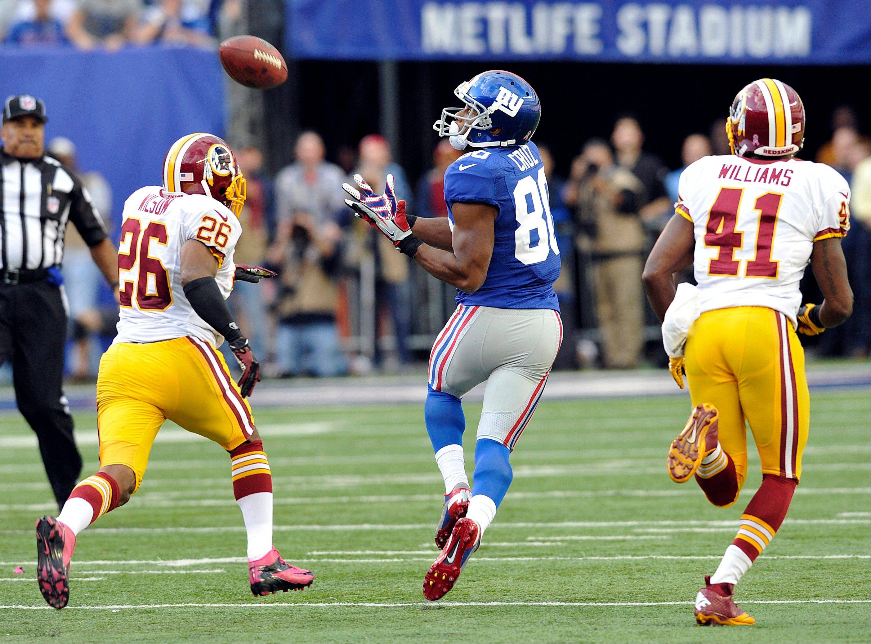 Giants wide receiver Victor Cruz catches the game-winning touchdown pass as Washington�s Josh Wilson (26) and Madieu Williams pursue him Sunday in East Rutherford, N.J.