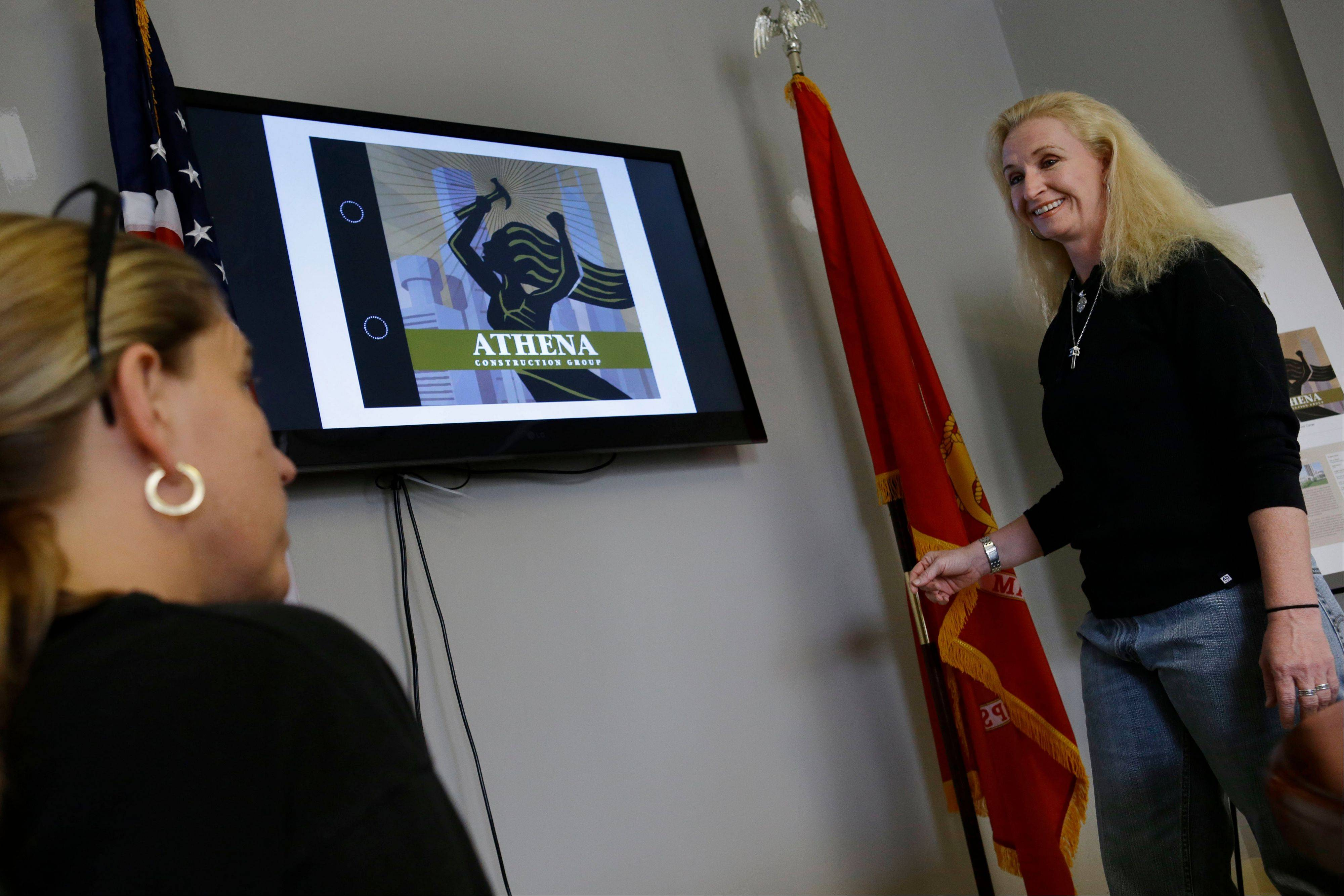 Amber Peebles, right, and Melissa Schneider, talk over a presentation about their business, Athena Construction Group, at their office in Dumfries, Va.